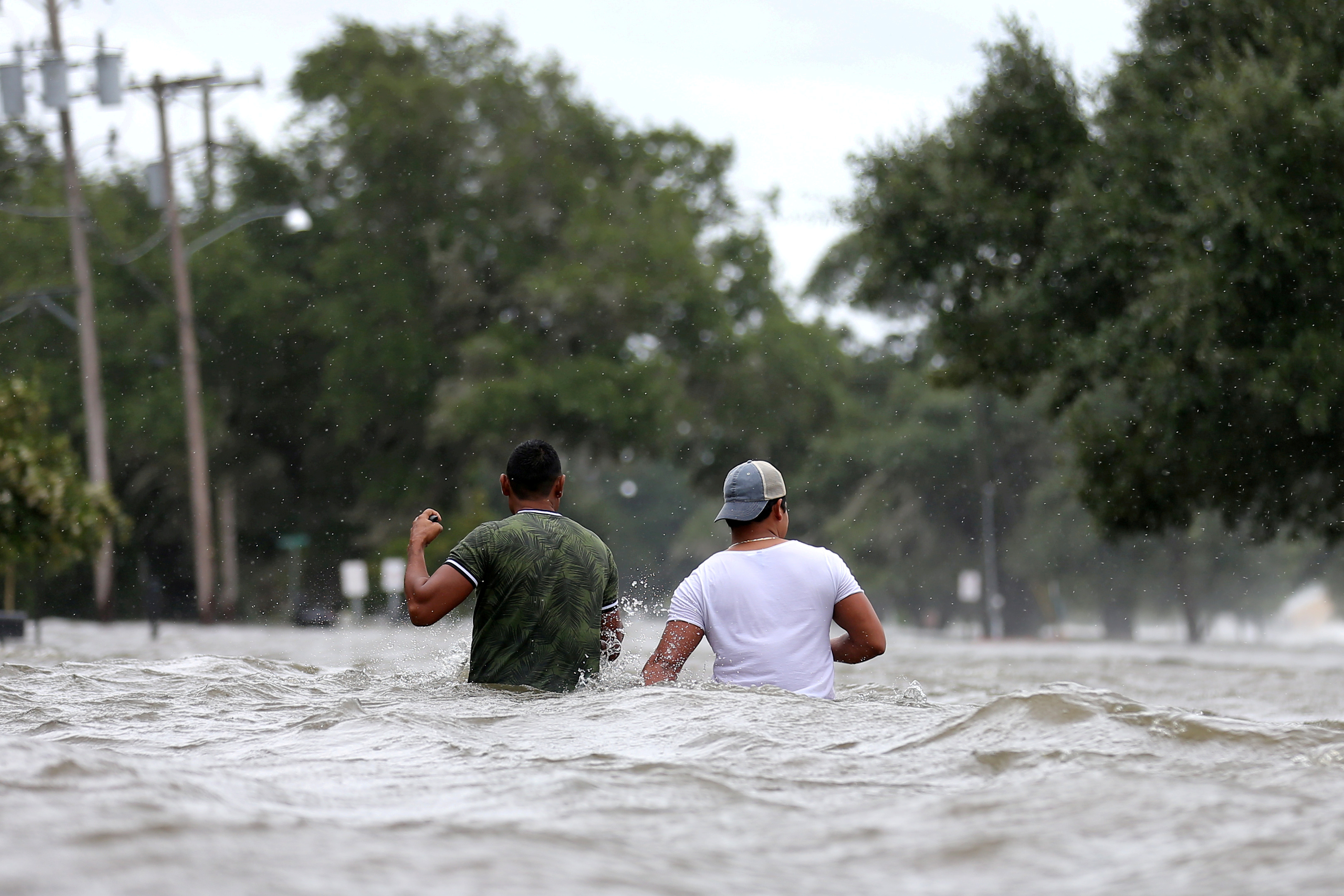 People wade through a flooded street after Hurricane Barry in Mandeville, Louisiana.