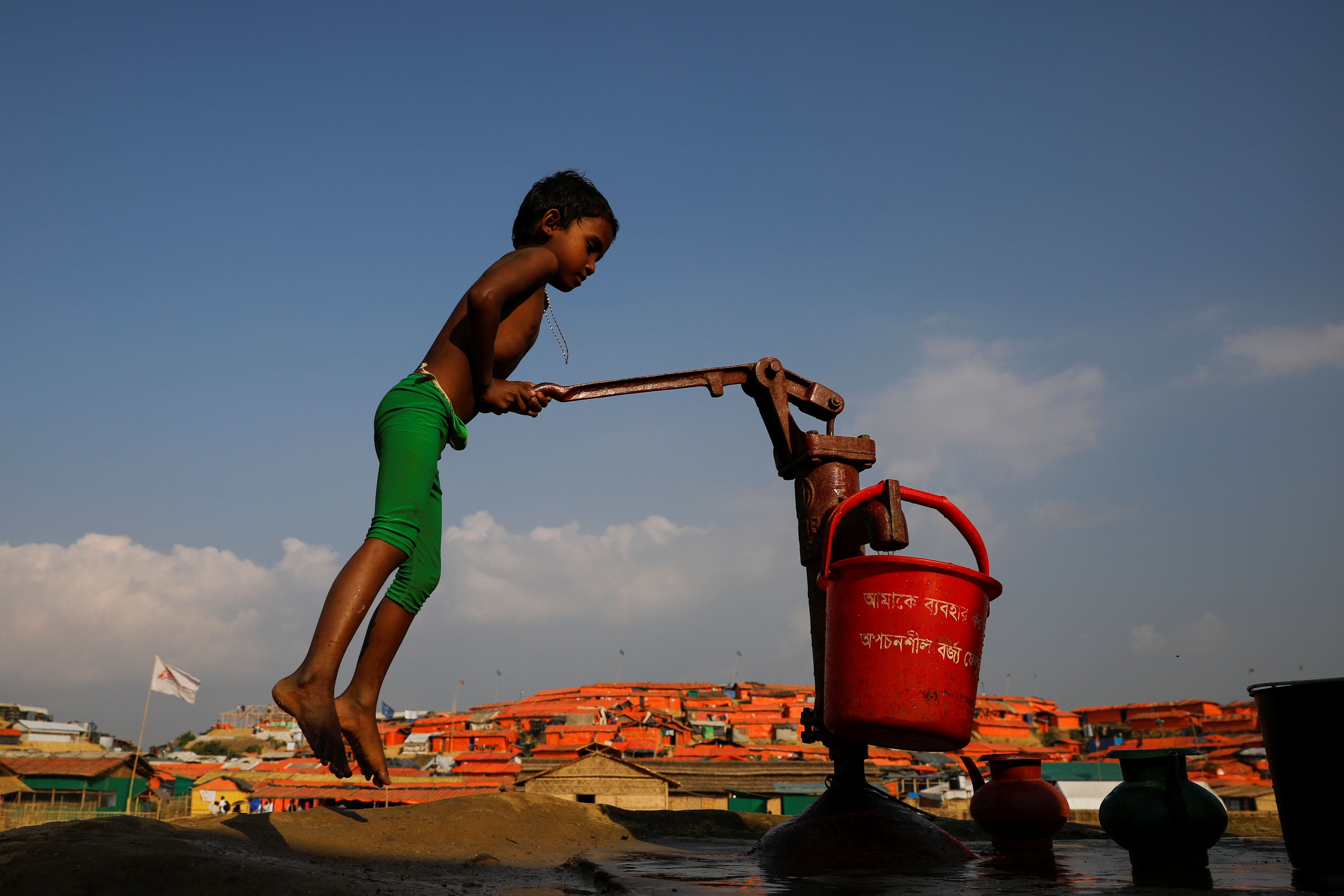 A Rohingya refugee child fills a bucket of water in Bangladesh.