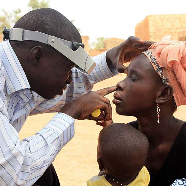 Technician doing eye exam during azithromycin mass drug administration training exercise near Ouagadougou, Burkina Faso.