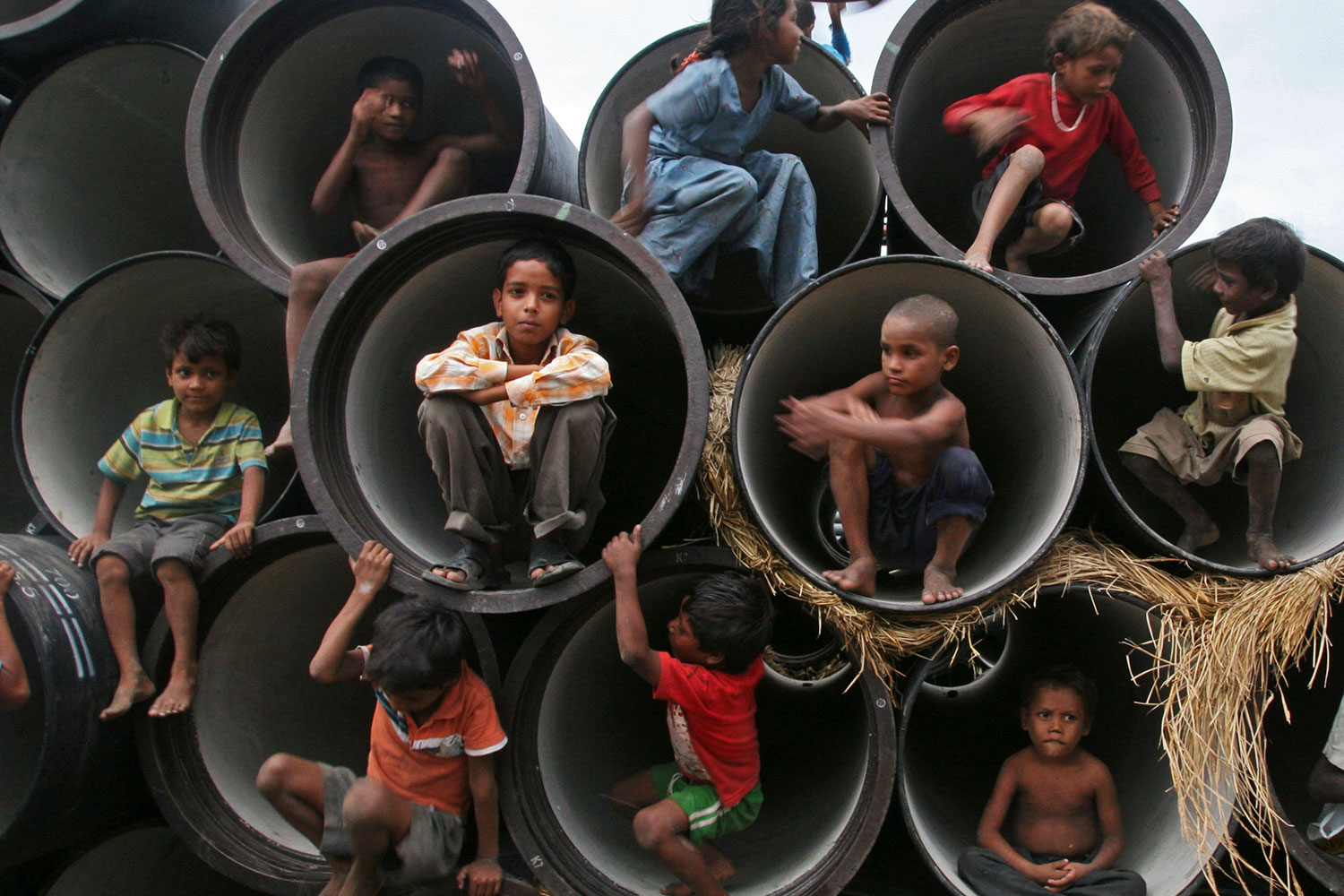 Children play in water pipes at a construction site on the banks of the Yamuna River on July 26, 2010in the northern Indian city of Allahabad. Picture shows several rows of large, concrete sewer pipes stacked on top of each other with their fat openings facing the camera. Each is large enough to fit one child huddled at the opening. About ten children can be seen climbing about on the feature. REUTERS/Jitendra Prakash