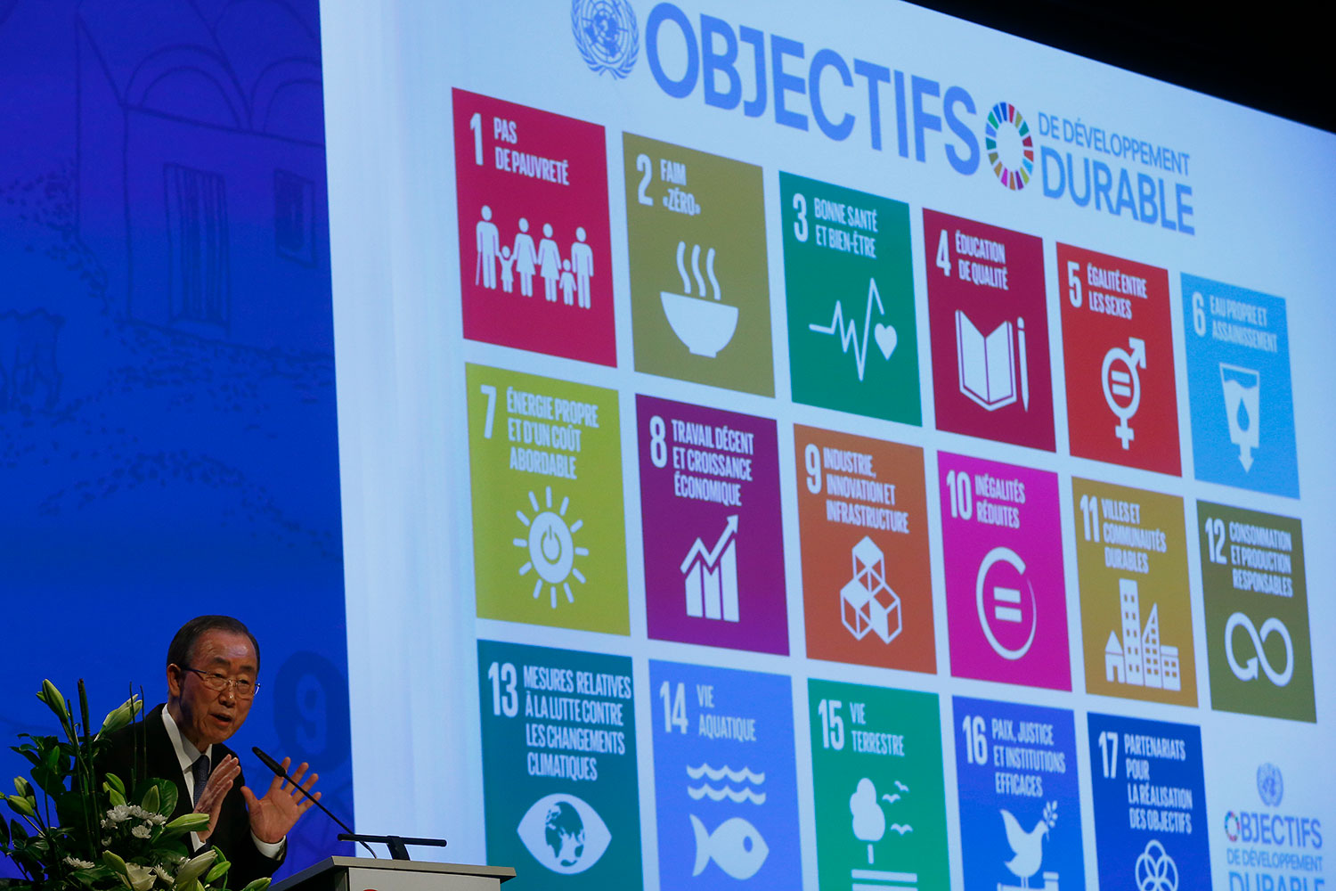 United Nations Secretary-General Ban Ki-Moon sits at a table on a stage with a large screen. The photo shows him in the corner of the frame. On the screen behind him are displayed pastel-colored icons representing the 17 goals of UN's 2030 Agenda for Sustainable Development.