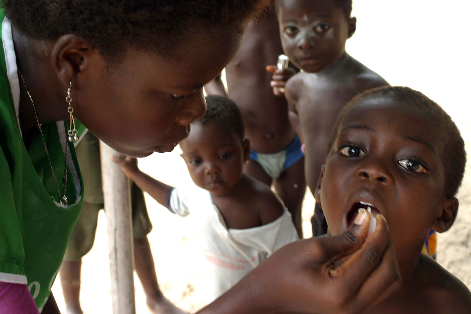 Picture shows a health care worker in a green uniform giving oral drops to a young boy who has his mouth open. Several other young children can be seen queued behind the boy.