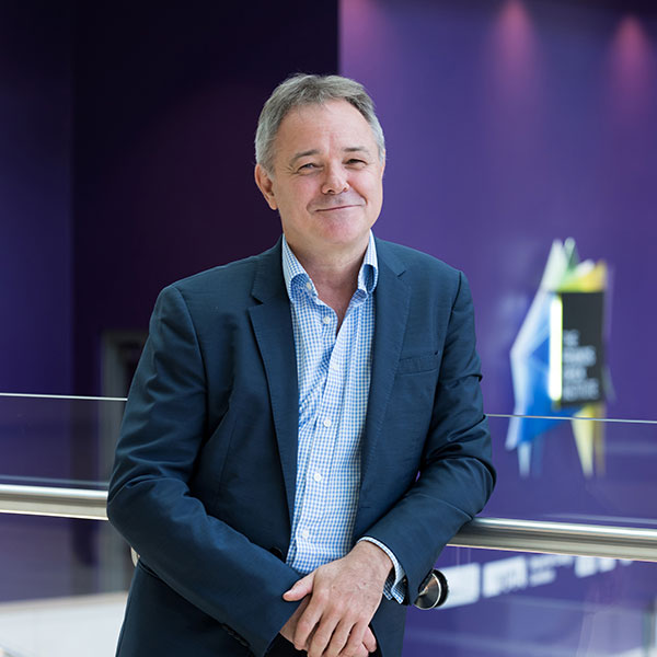 Jeremy Farrar, Director of the Wellcome Trust. The picture shows Farrar wearing a blue shirt and blazer, smiling as he leans on sleek railing and standing out against a highly bokeh background. FRANCIS CRICK INSTITUTE/Dave Guttridge