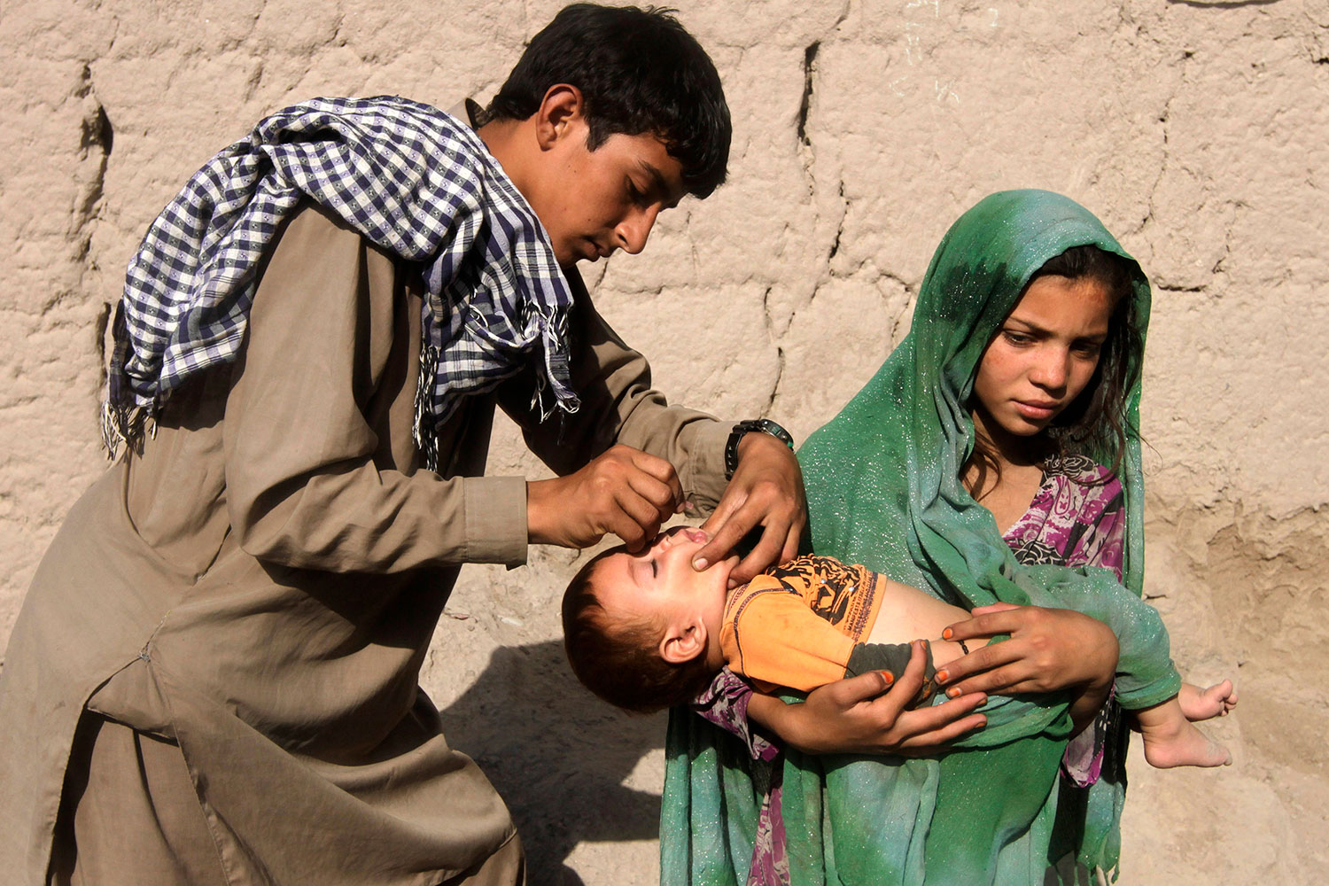 A child receives polio vaccination during an anti-polio campaign on the outskirts of Jalalabad, Afghanistan on August 18, 2014. In the photo a young man with a black-and-white checkered scarf slung over his shoulder administers drops to a baby held in the arms of a young woman wearing a bright green headdress.