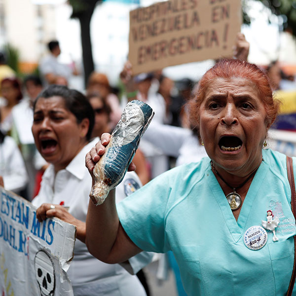 Health care workers protesting shortage of medical supplies outside a hospital in Caracas, Venezuela on November 19, 2019. The picture shows an older woman in the foreground wearing blue hospital scrubs shouting and looking slightly off camera. She is surrounded by other protestors, many of whom are waving protest signs and also shouting. REUTERS/Carlos Garcia Rawlins