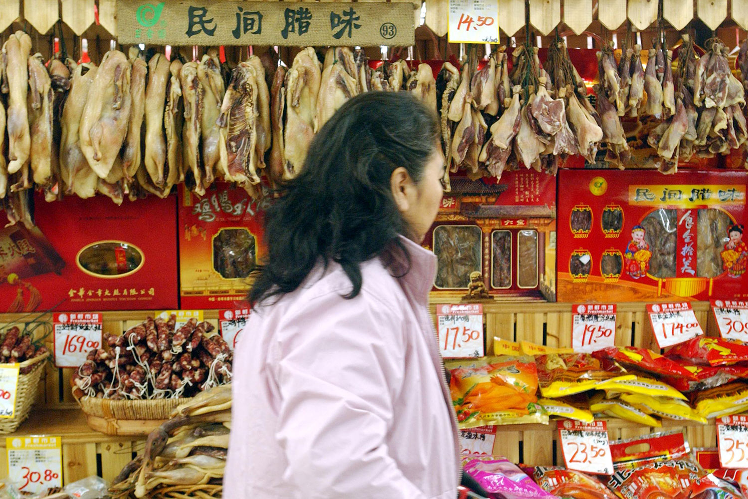 Walking by the camera is an older woman with her hair pulled back wearing a dull pink jacket. She walks perpendicular to the direction of the camera and is looking away, at the various foods on display. Behind her is a dizzying array of red- and yellow-hued dried meats and fishes, sausages and packages.