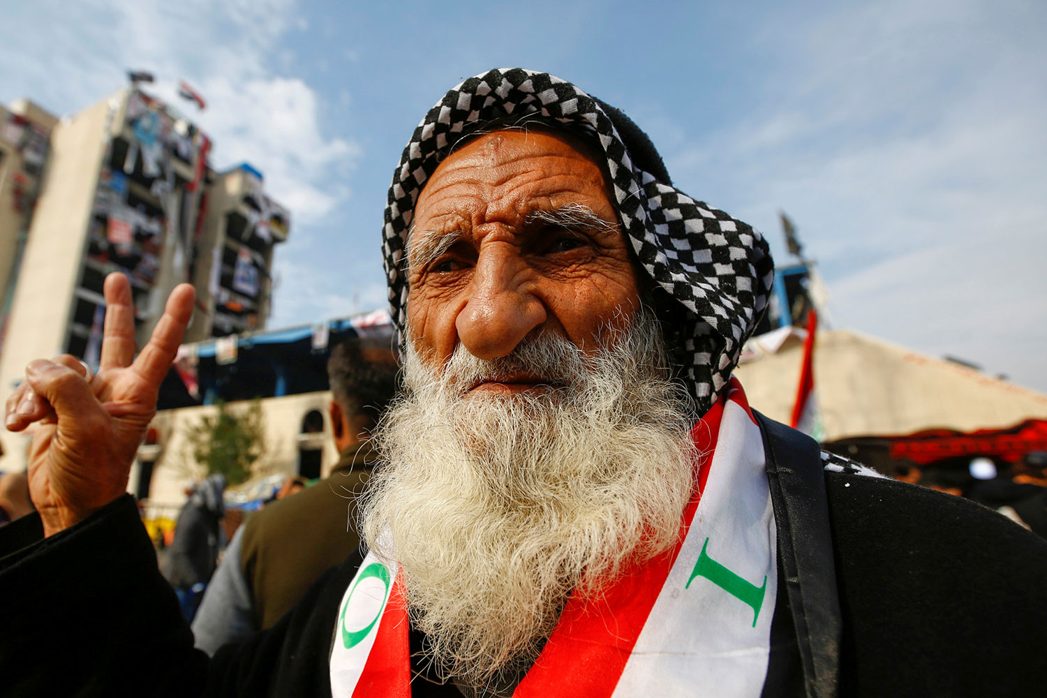 An elderly demonstrator poses for the camera as he makes a V-sign during ongoing anti-government protests, in Baghdad, Iraq, December 10, 2019. He has a black-and-white checkered scarf tied on his head and a red and white sash with green accents, around his neck. He has a very long white beard and friendly eyes. REUTERS/Alaa al-MarjaniSELECT