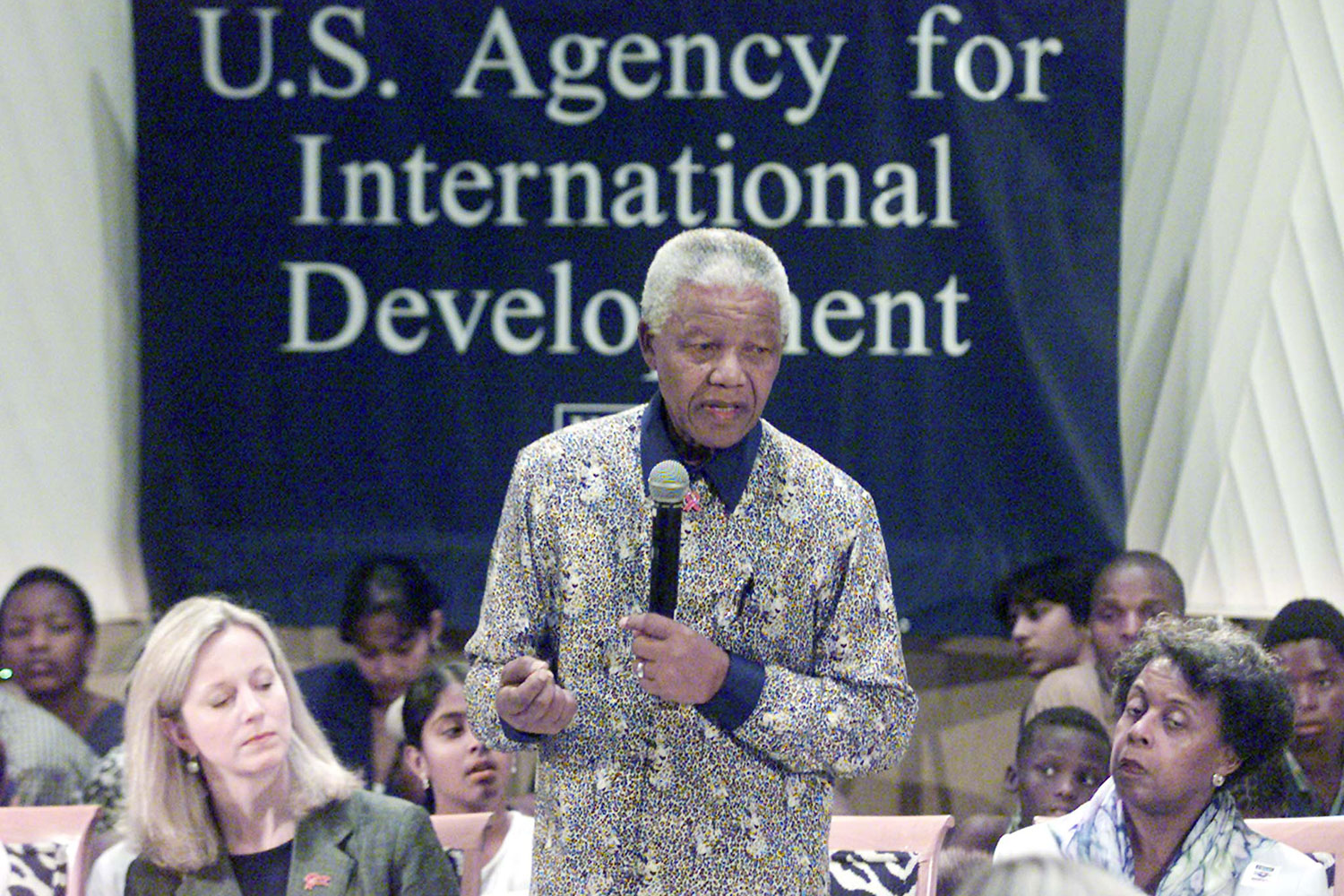 "Image shows Nelson Mandela speaking into a microphone before a sign that reads, ""U.S. Agency for International Development"" at the International AIDS Conference in Durban, South Africa on July 14, 2000. He is standing and is surrounded by people who are sitting and appear to be listening intently."