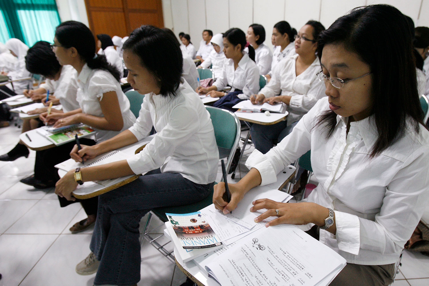 "Picture shows a classroom with several rows of nurses at desks, all with white shirts and black pants. They are taking notes and one of them in the foreground has a book on her desk titled, ""Japanese Phrase Book."""