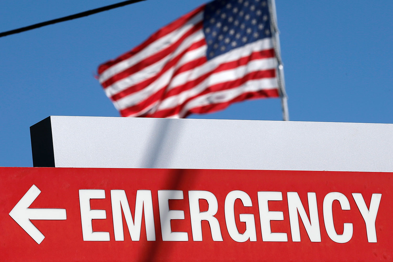 "An entrance sign to the Texas Health Presbyterian Hospital in Dallas, Texas, on October 4, 2014. The sign says ""EMERGENCY"" and points to the left. In the background we can see an American flag billowing against a brilliant clear blue sky. REUTERS/Jim Young"