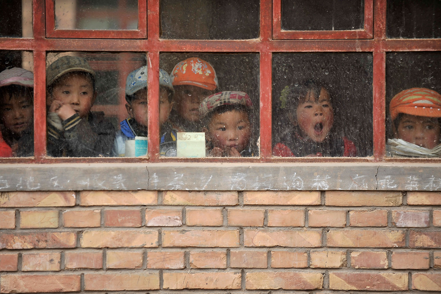 Children look out from their classroom in a (truly) rural primary school in Min County, Gansu Province, China on June 1, 2011. The school, with five teachers and 102 students, is on a high mountain. We see the adorable faces of several small children looking out weather-beaten window panes hung on a yellow brick wall. Faded chalk writing of chinese characters can be seen scribbled on the concrete sill. REUTERS photo.