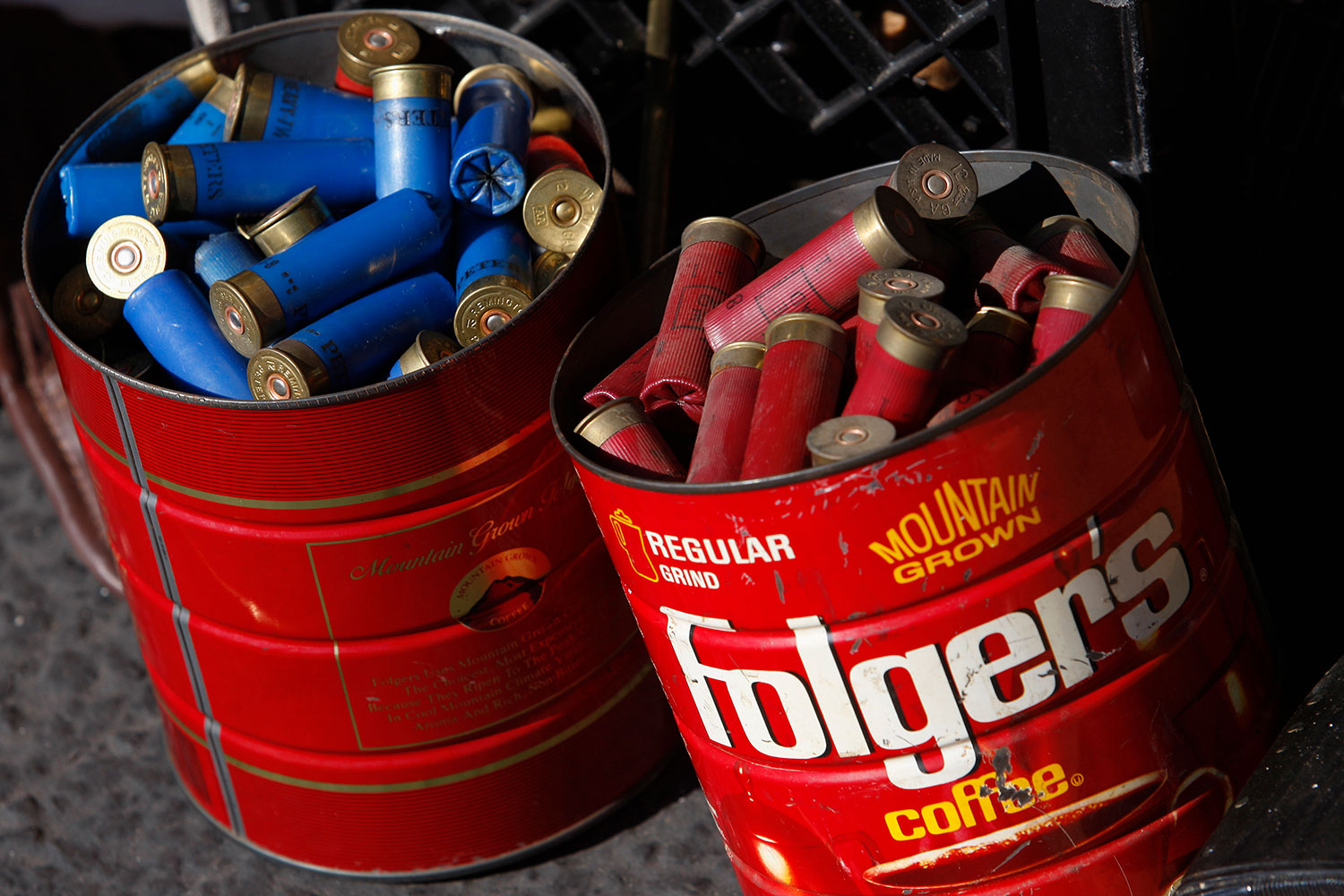 "Old coffee cans of shotgun shells dropped off to the Los Angeles County Sheriff's Department at the ""Gifts for Guns"" buyback in Compton, California on January 21, 2013. Picture shows two bright red, rusted out coffee tins filled to the brim with shotgun shells, red shells in the first tin, blue in the second. REUTERS/David McNew"