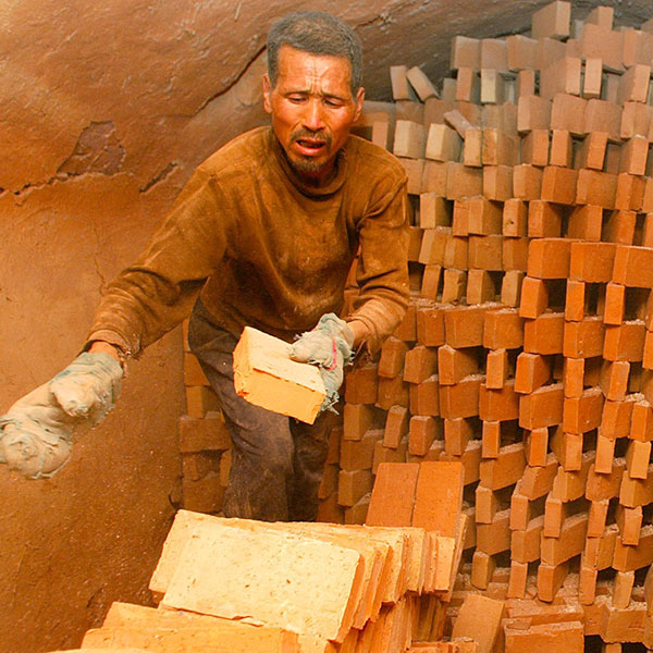 Chinese men work at a brick production plant in Xian, northwest of China's Shaanxi province on April 27, 2005. The photo shows a man pulling bricks off a stack where they were presumably kiln fired and placing them into a stack in the foreground. the overall color of the photo is brick red, suggesting that the dust is everywhere.