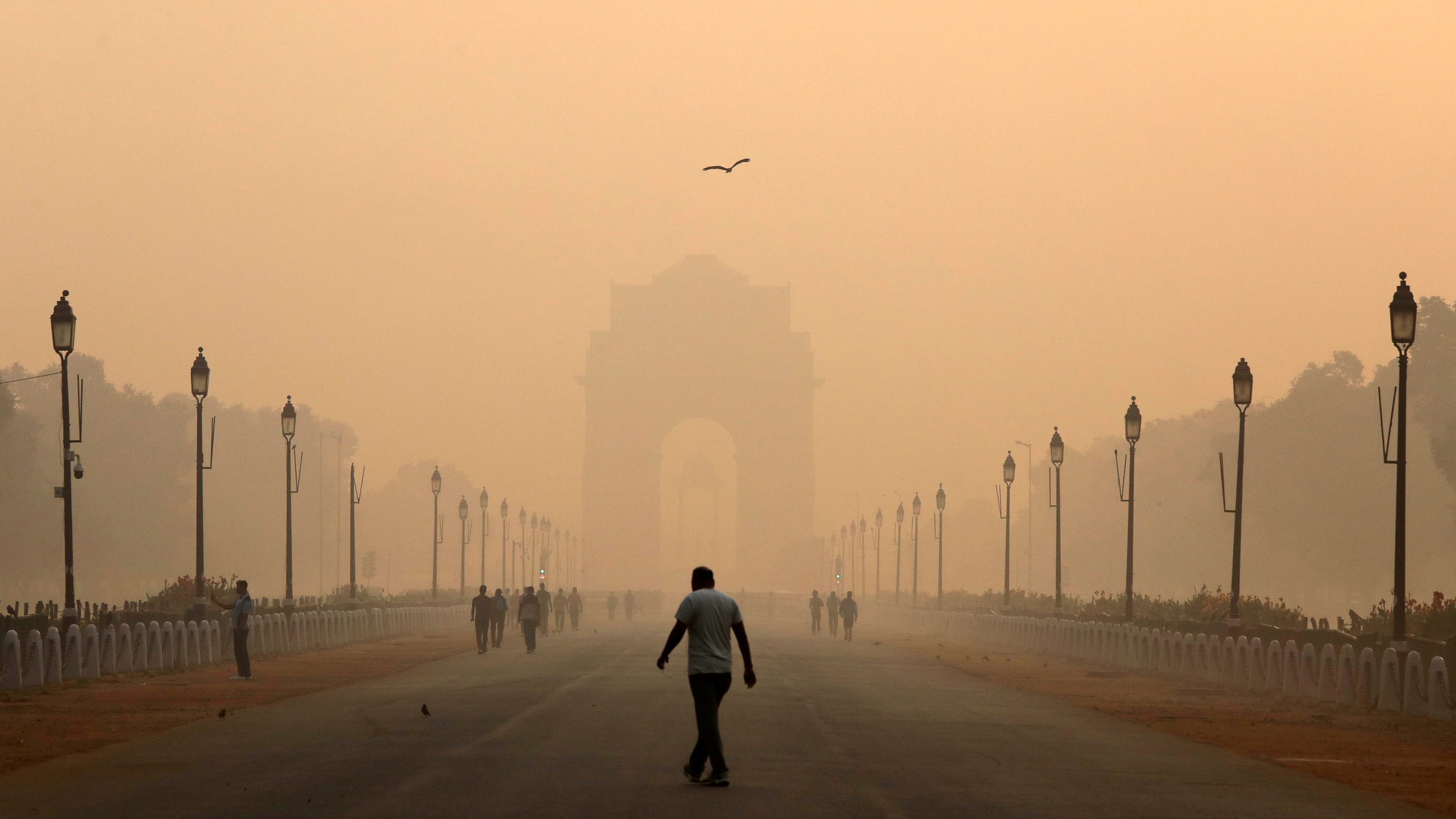 Photo shows a man in the distance and a grand architectural structure in the far distance, which is hard to see through the smog.