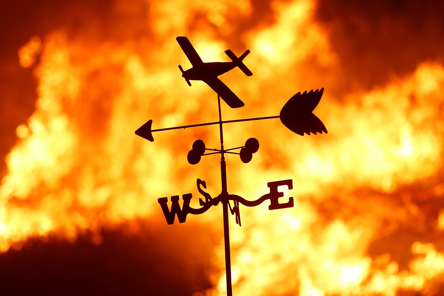 "A weather vane is pictured on a ranch during the Creek Fire in the San Fernando Valley north of Los Angeles, in Sylmar, California on December 5, 2017. Picture shows a thin metal toy-like vain with a plane, and arrow and a ""NESW"" directional indicator silhouetted against a burning fire. REUTERS/Jonathan Alcorn"