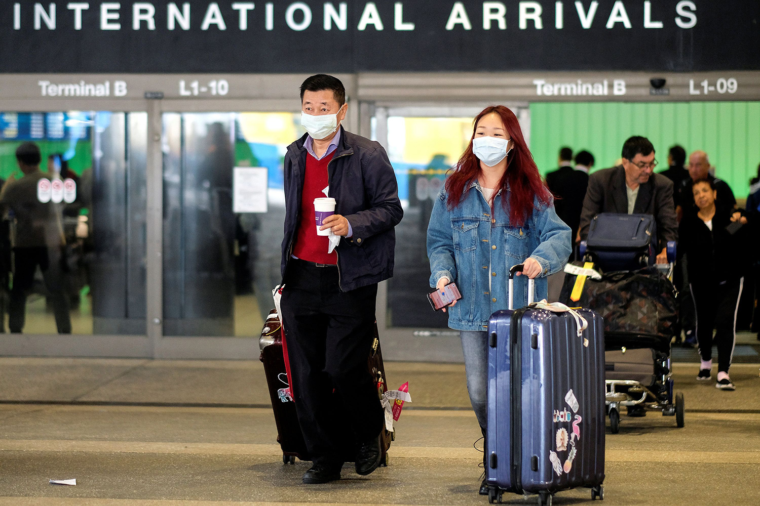 "Image shows two travelers with their bags marching out of a gate that says ""International Arrivals"" in bold letters. They are both wearing dust masks."