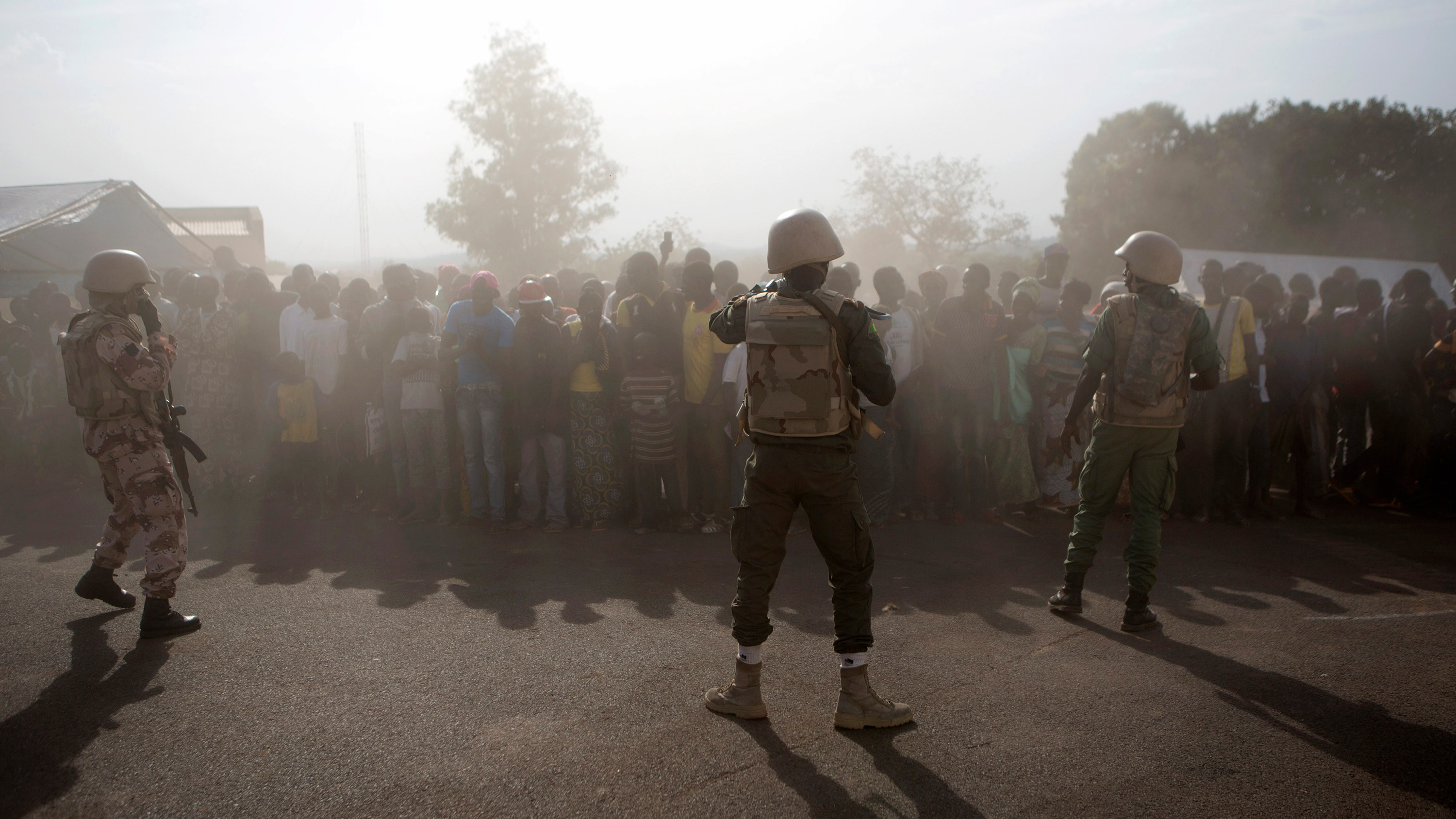 he picture shows a large crowd shrouded in what appears to be early morning mist with a thin line of heavily armed soldiers wearing combat fatigues standing between them and the camera.