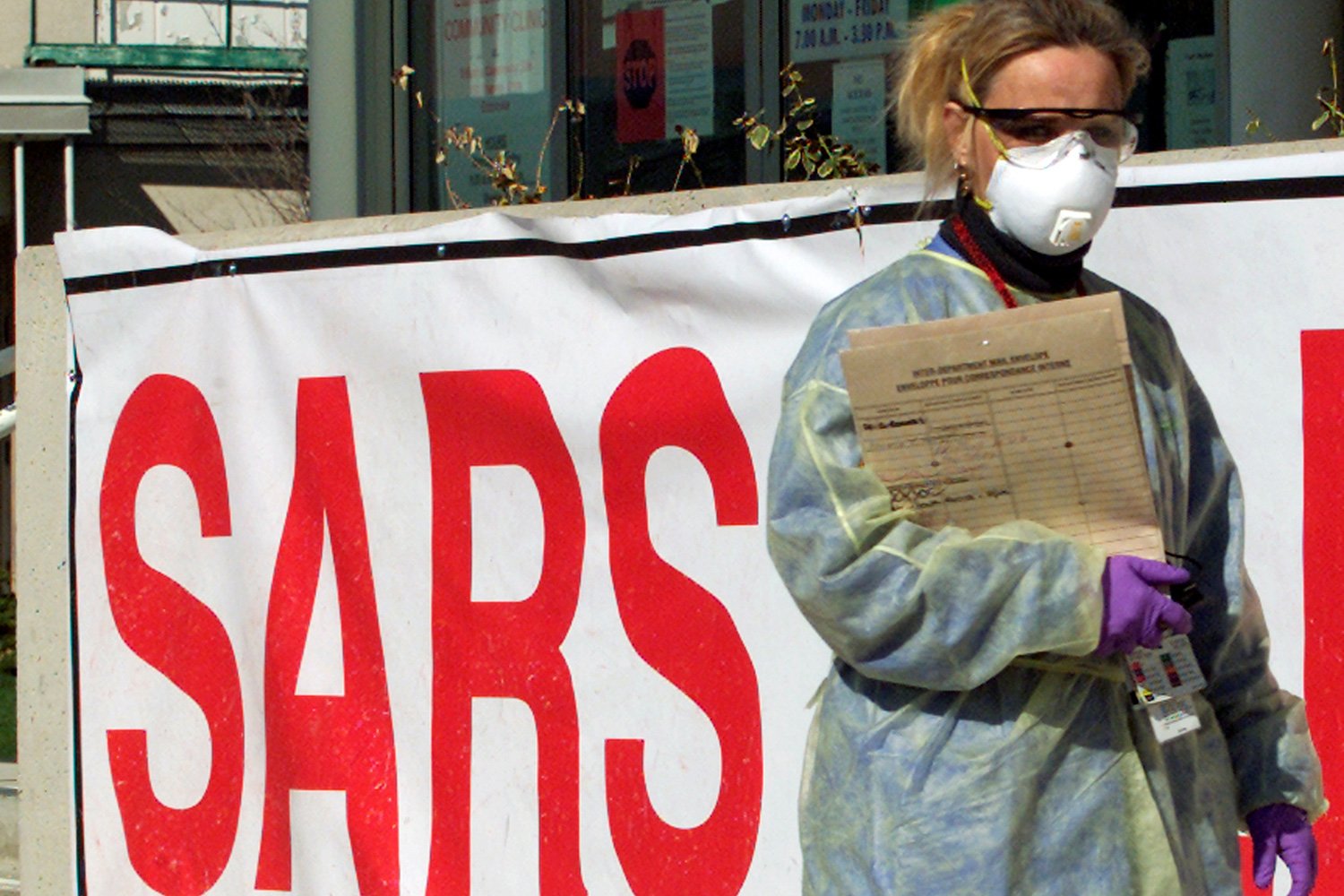 "The image shows a woman wearing full protective gear, including eye protection and a surgical mask in front of a hospital adorned with a huge sign that says ""SARS"" in bright red letters."