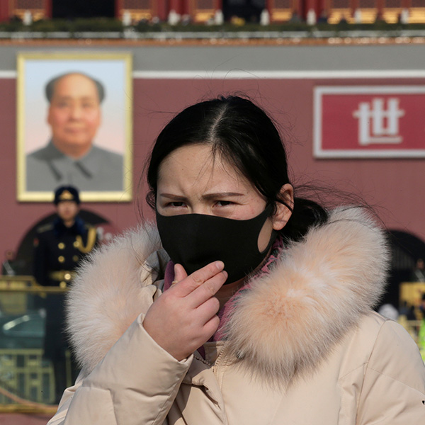 A tourist wearing a mask visits Tiananmen Square in Beijing, China January 22, 2020. The photo shows a woman in a black mask in the foreground with a huge portrait of Chairman Mao visible in the background, along with a uniformed officer standing guard. REUTERS/Jason Lee