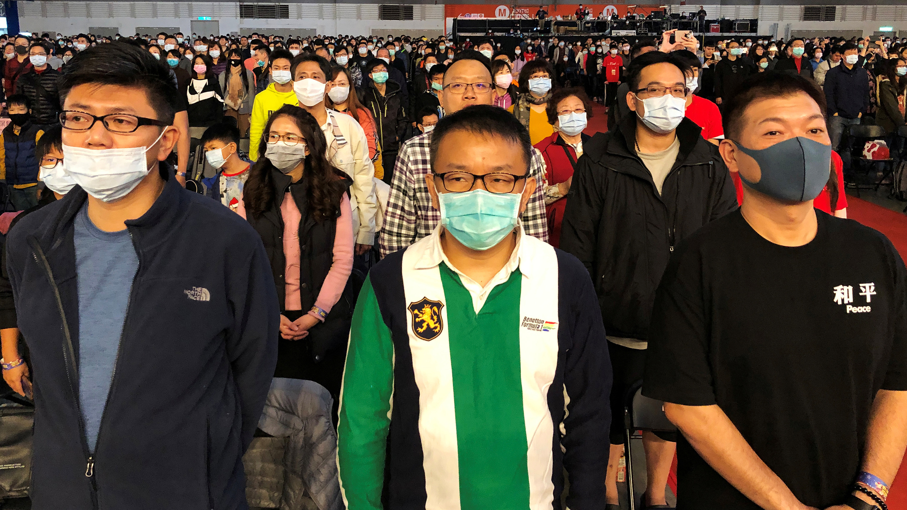 The photo shows a massive arena-like space filled with people, almost all of whom are wearing face masks.