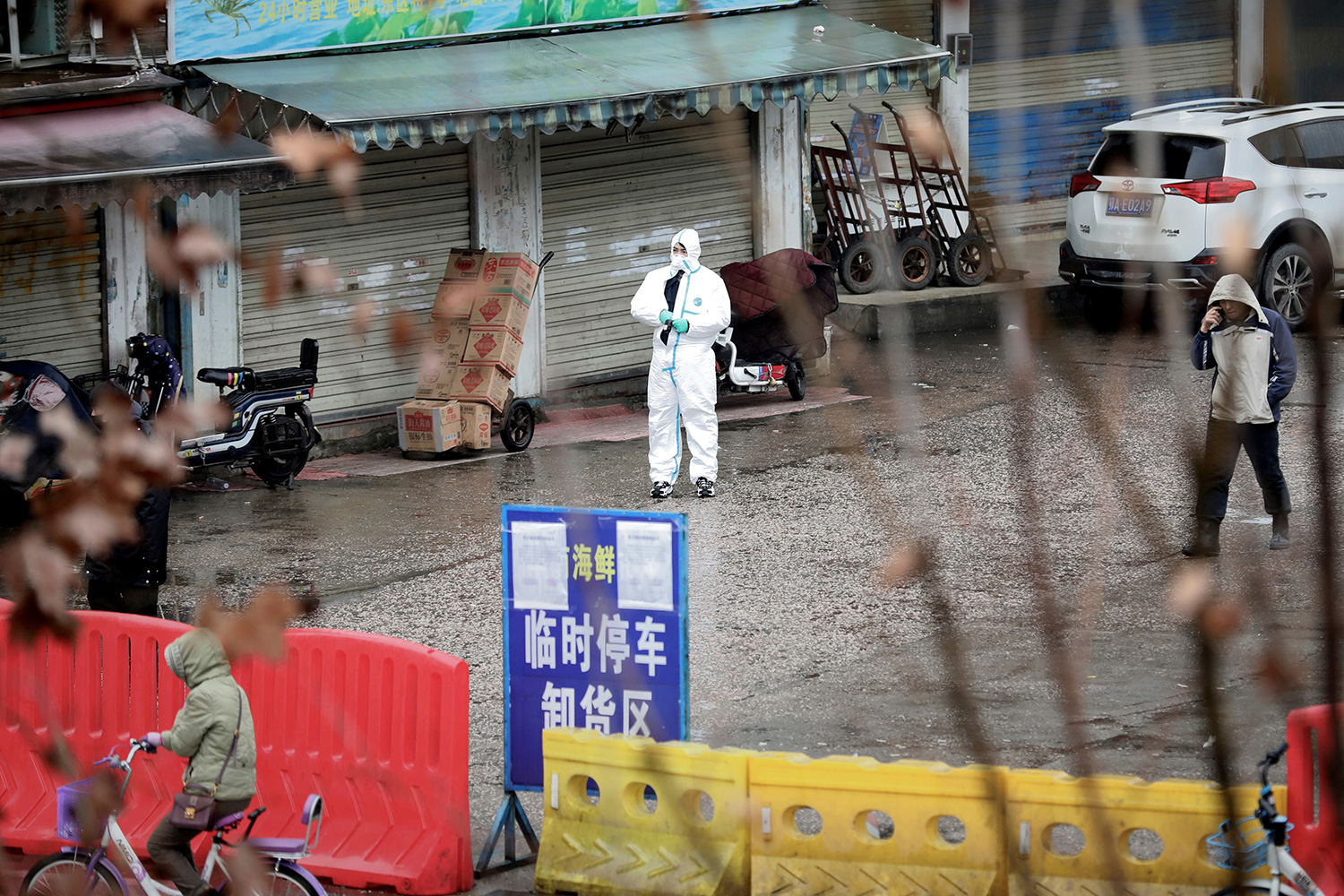 Picture shows the entrance to the market from a distance with a man wearing full protective gear stands out front.