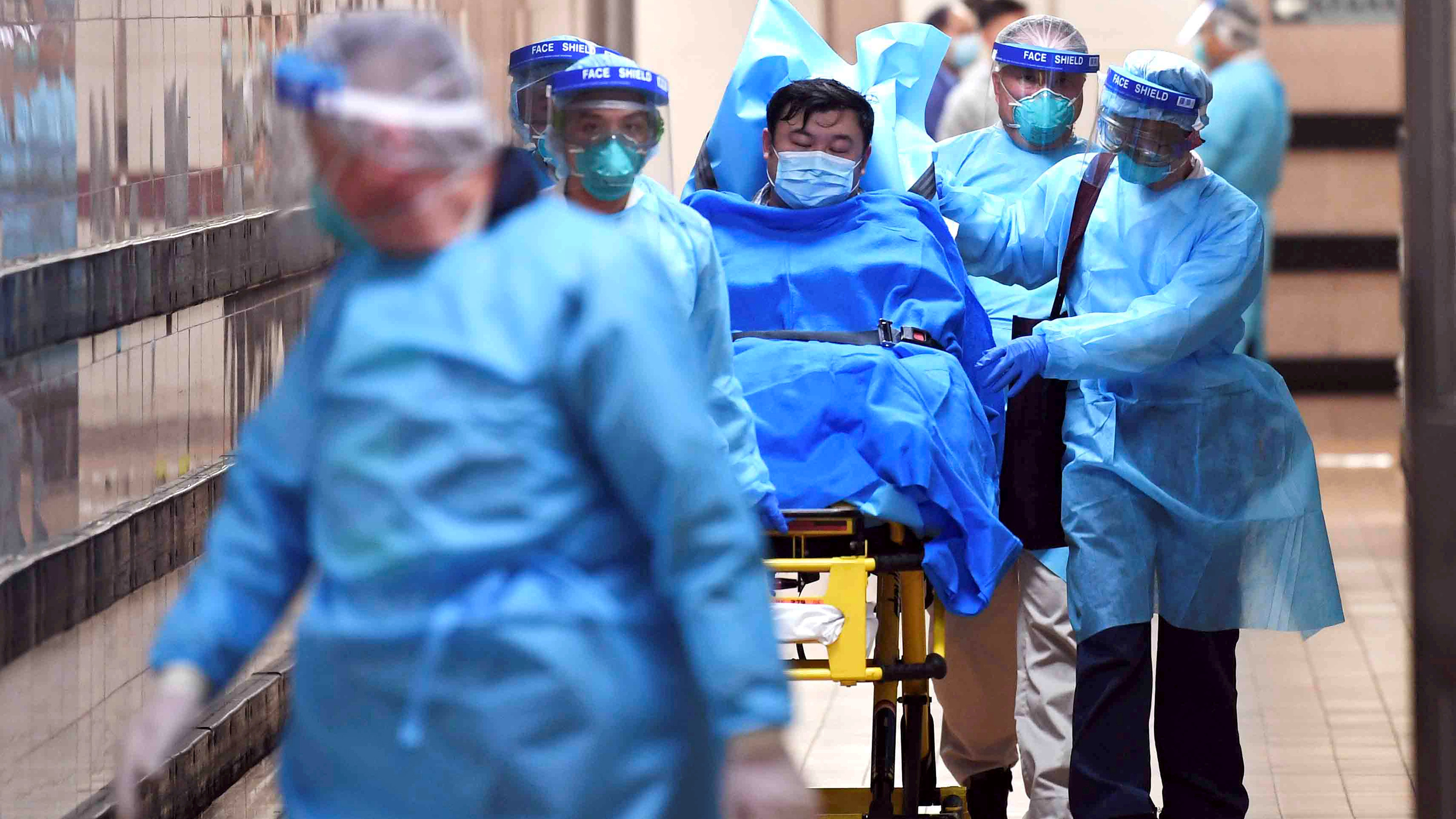 Picture shows a patient on a wheeled bed surrounded by four health care providers moving him with another caregiver walking in front. They all are covered head-to-toe in blue protective gear.
