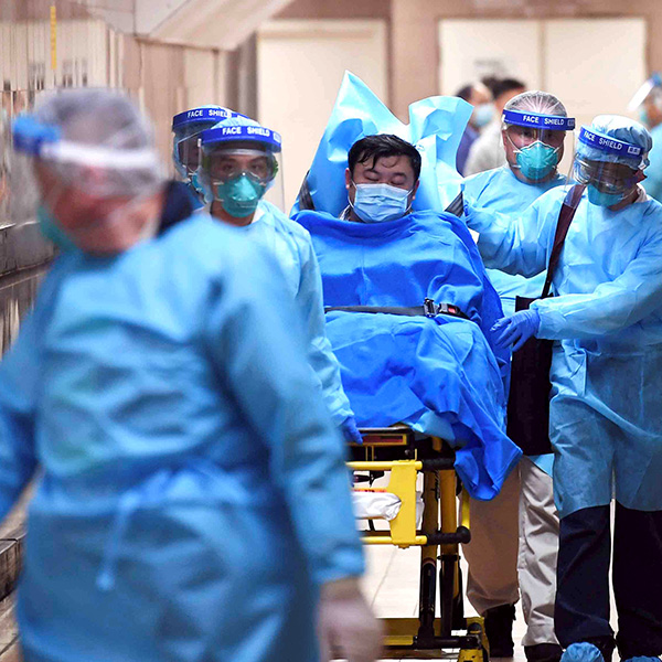 Medical staff transfer a patient of a highly suspected case of a new coronavirus at the Queen Elizabeth Hospital in Hong Kong on January 22, 2020. Picture shows a patient on a wheeled bed surrounded by four health care providers moving him with another caregiver walking in front. They all are covered head-to-toe in blue protective gear. REUTERS/cnsphoto