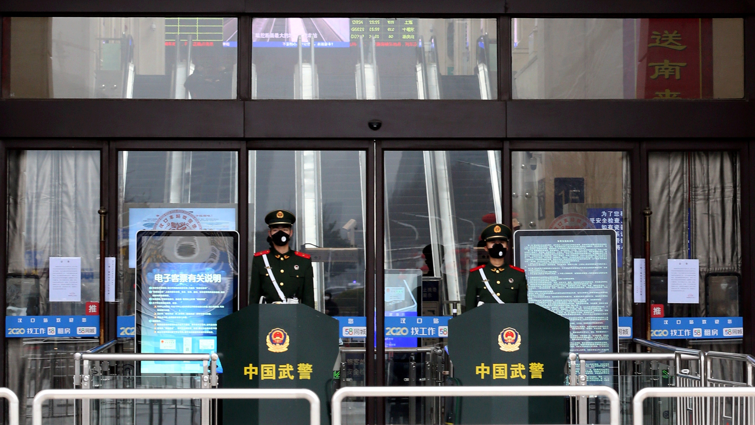 The photo shows the shuttered front of the grand entrance hall to the station with two soldiers wearing face masks out front.