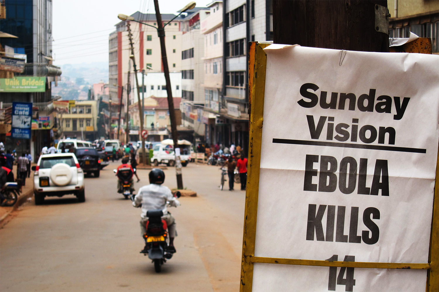 The photo shows a busy urban street with a sign announcing the Sunday paper's headline, Sunday Vision, EBOLA KILLS 14, Sunday July 29, 2012.