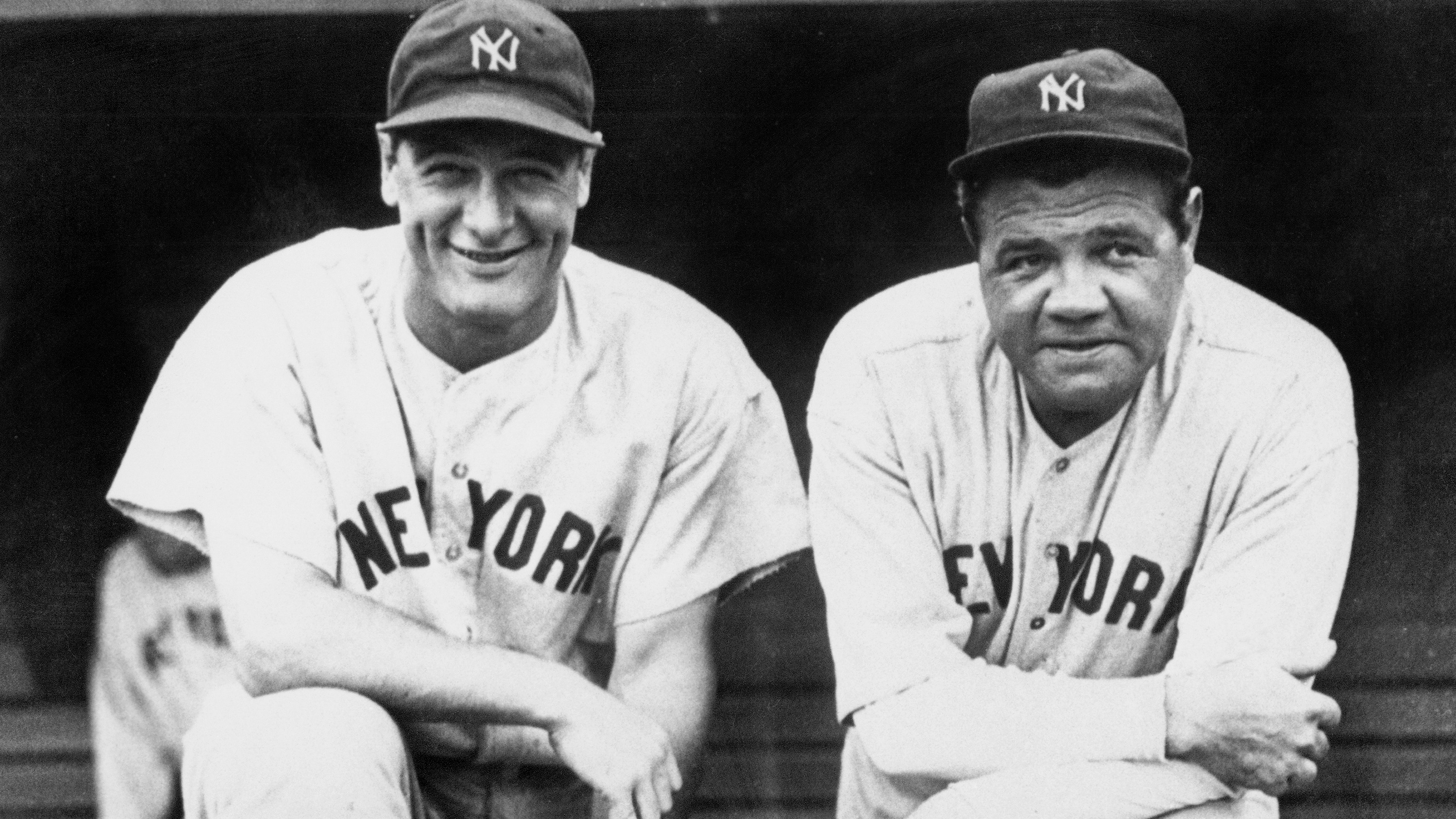 The photo shows Lou Gherig smiling while leaning on one knee propped on a dugout bench next to Babe Ruth.