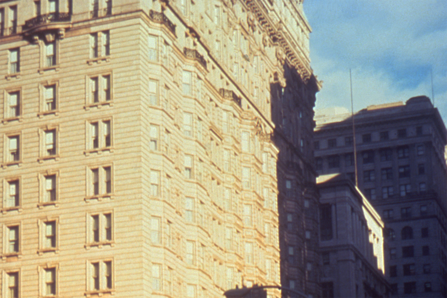 The photo shows an old, magnificent stone building against a bright blue sky. It's a grainy photo, suggestive of a poor quality color film stock or a cheap camera.