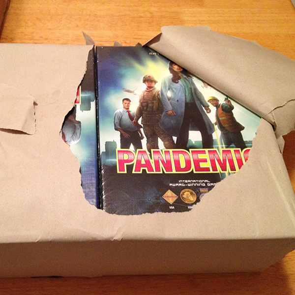 A bundle of the original Pandemic board game boxes. Photo a large armful-sized package neatly wrapped in brown paper. The paper is slightly torn open, revealing eight new boxes of the game Pandemic. Photo courtesy of Matt Leacock