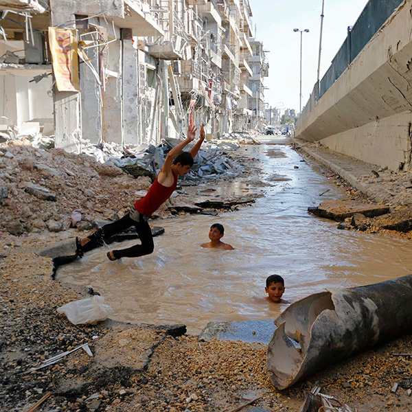 A boy dives into a crater filled with water in Aleppo's al-Shaar district on July 10, 2014. Activists said the crater was caused by barrel bombs dropped by forces of Syria's President Bashar al-Assad. The photo shows a boy leaping in mid-air into a water-filled hole. The water is muddy brown, and two other boys can be seen swimming in the hole with their heads bobbing out. Surrounding them is rubble. This is a powerful image. REUTERS/Hosam Katan