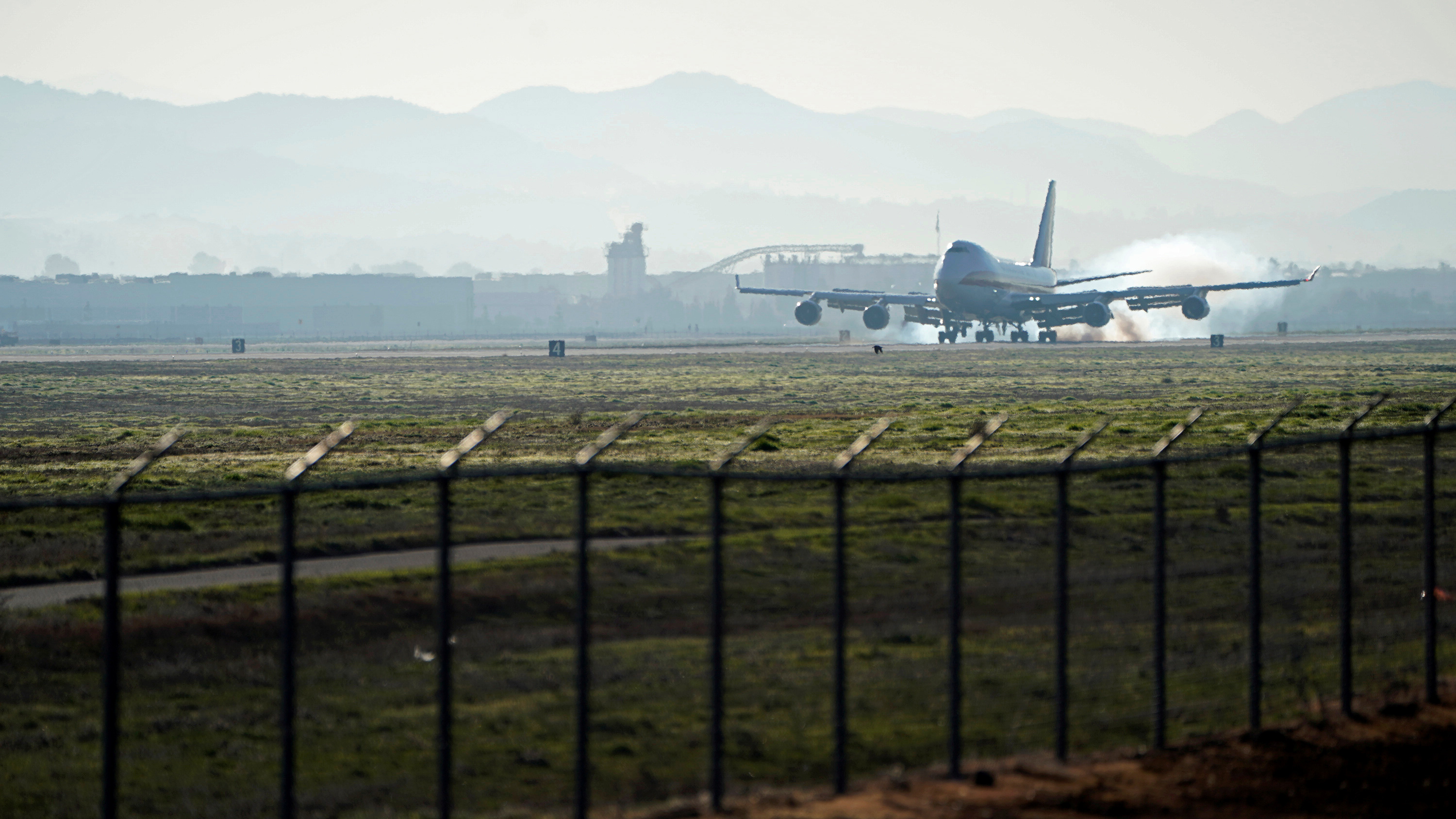 Photo shows a plane touching down in the distance from behind a security fence.
