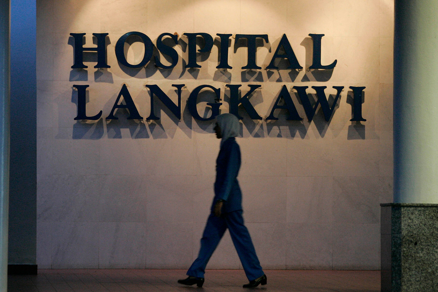 Photo shows a large hospital sign with a tall nurse walking by in front of it.