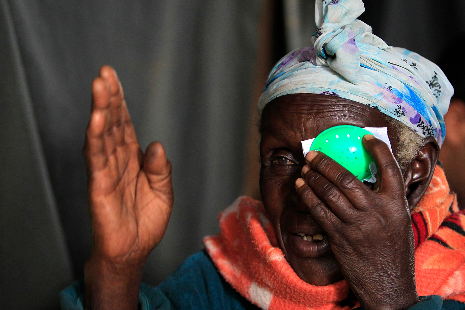 The photo shows a mature woman wearing a bright orange scarf taking an eye test, holding a green patch to her left eye and raising her right hand in front of her face.