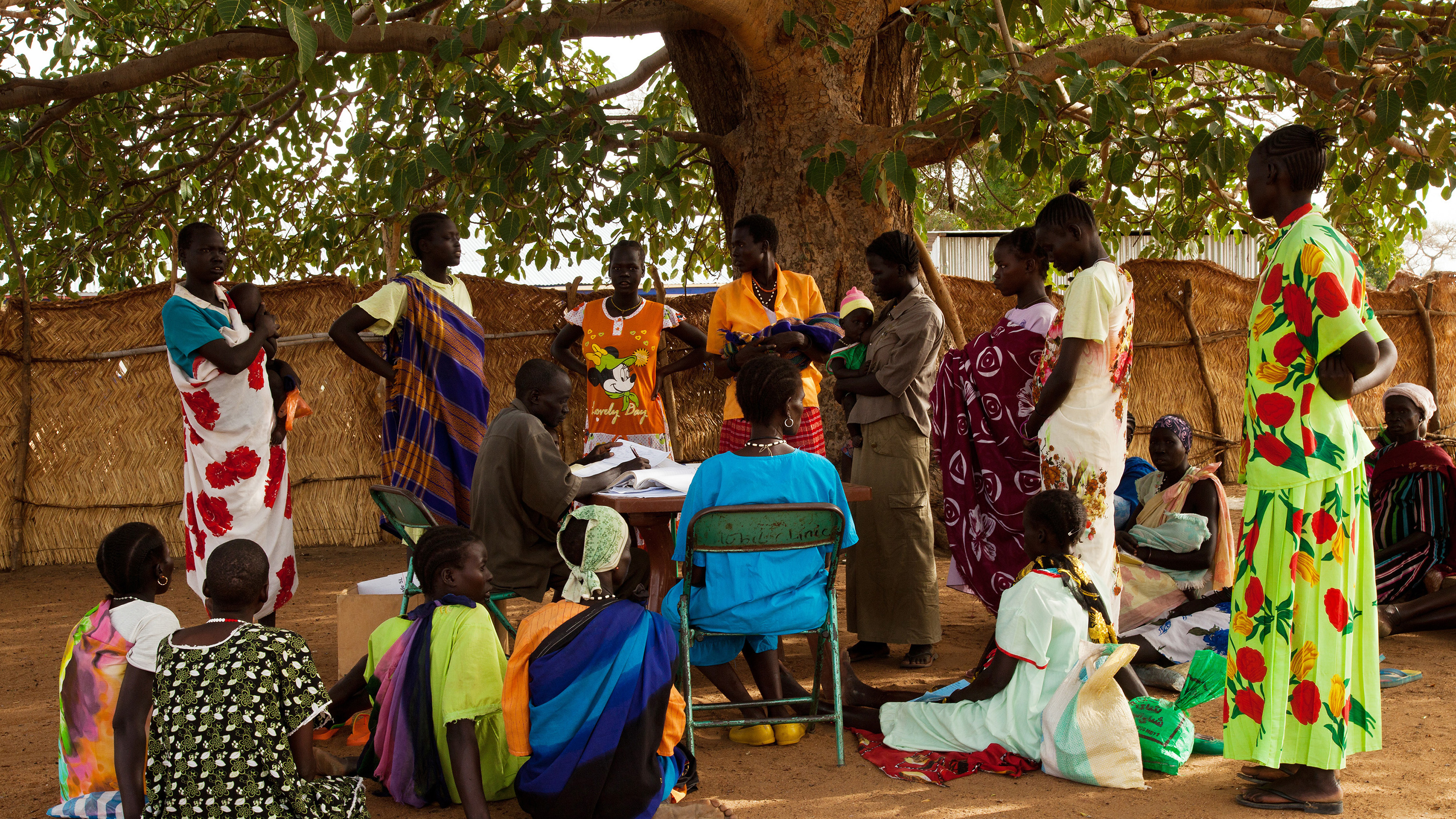 Picture shows a group of people, many of whom are wearing brightly coloured clothing, gathered under a tree, some sitting, some standing.