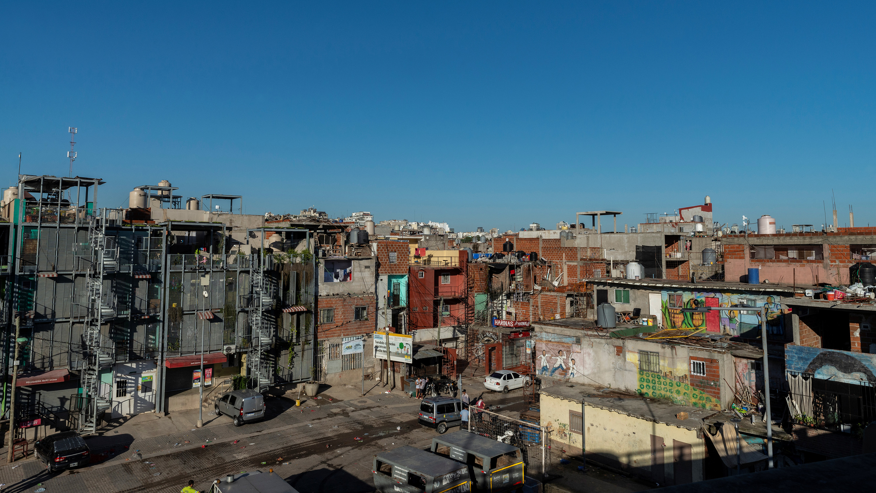 Photo shows a densely-packed brick and concrete community with box-like structures against a brilliant blue sky.