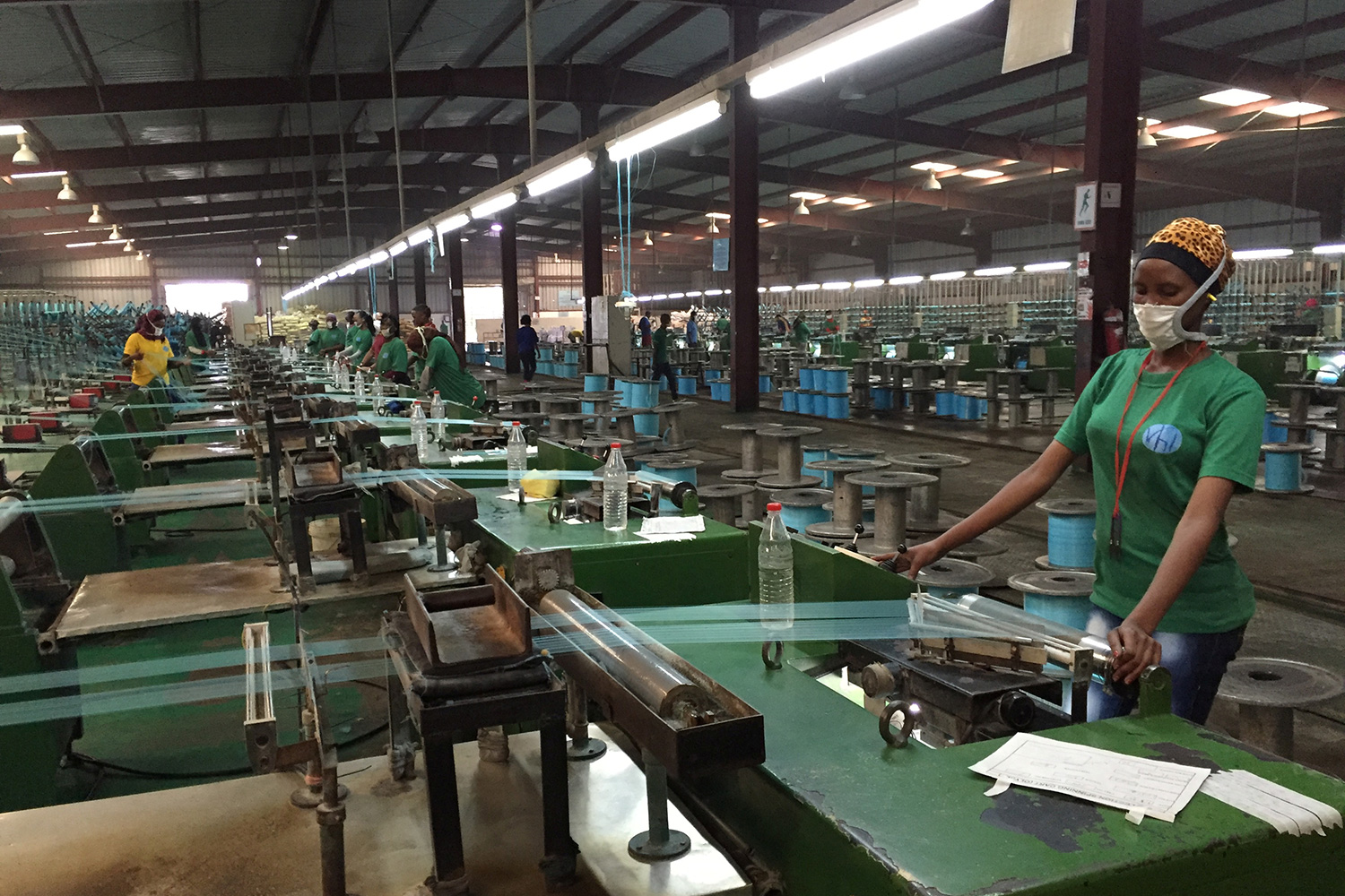 The image shows a large factory filled with machines and several workers at the controls of what appear to be industrial looms stretching fabric fibers.