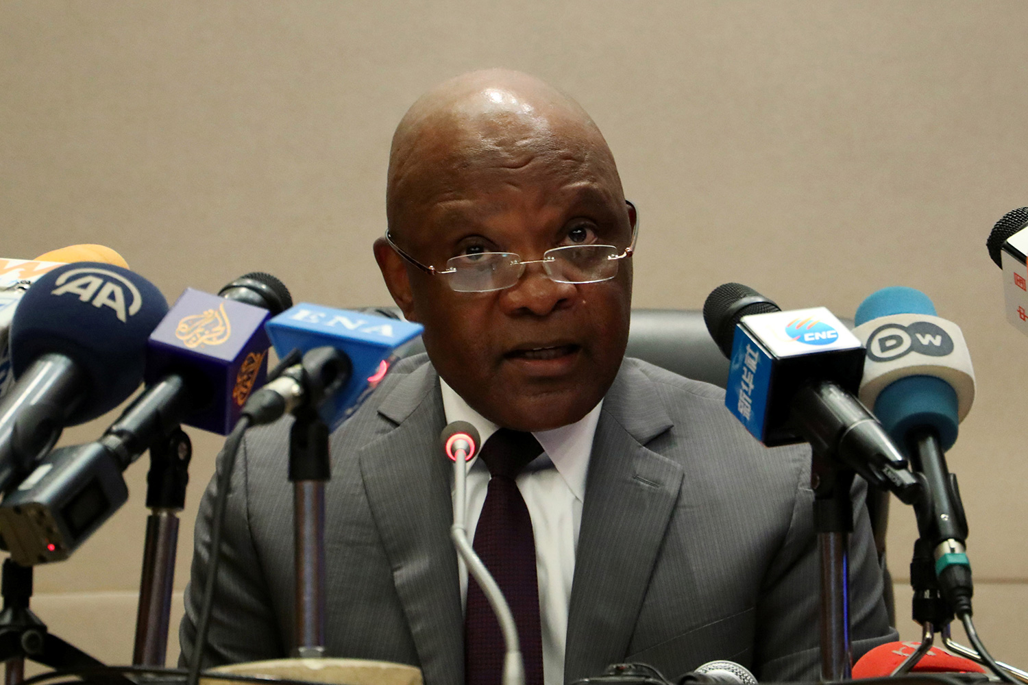 Photo shows the African CDC director speaking in front of a bank of microphones at a press conference.