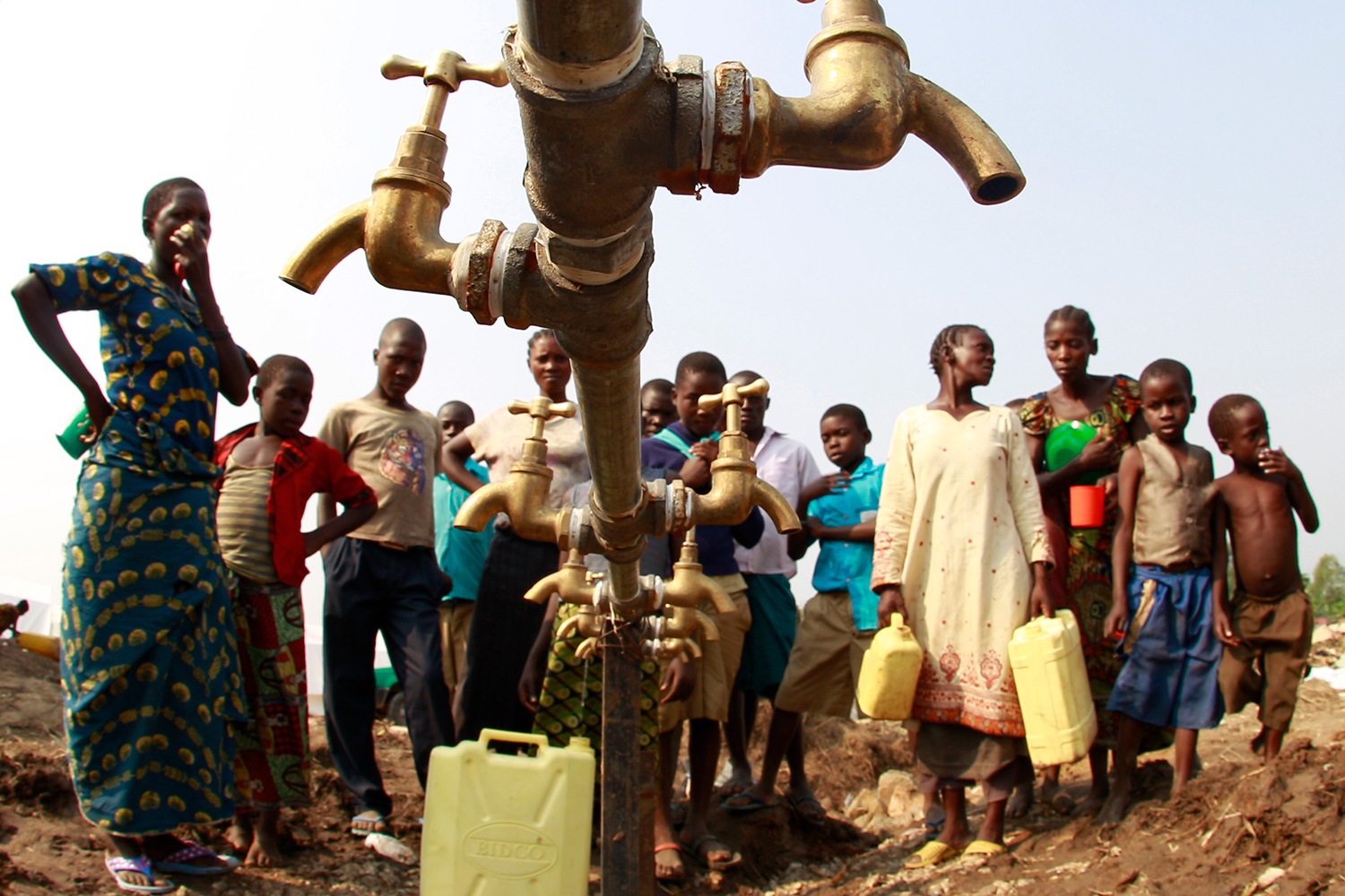 The photo shows a crowd of people around a metal water pipe with no water flowing.