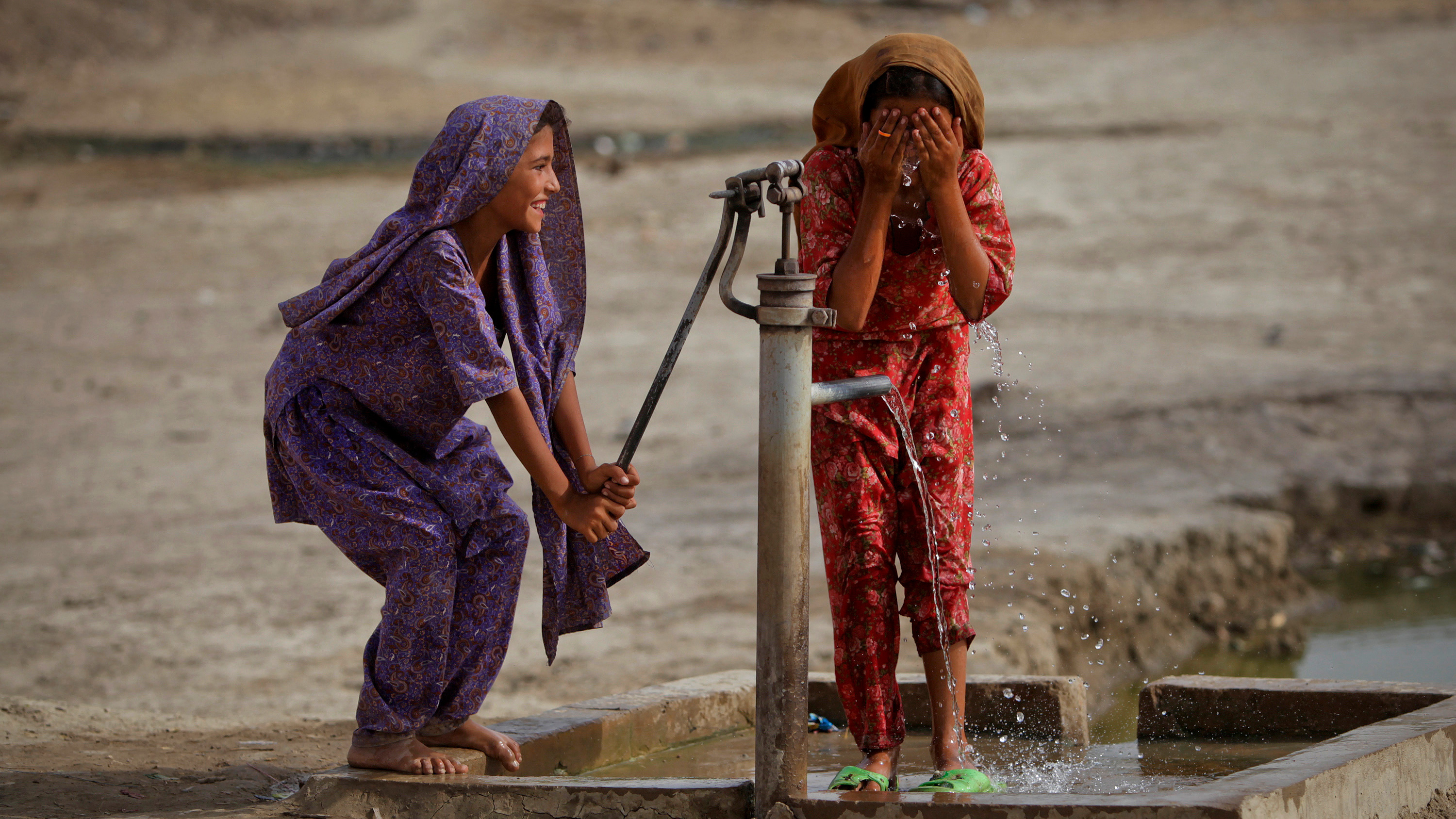 The picture shows two girls, one pumping, the other washing, and both laughing.