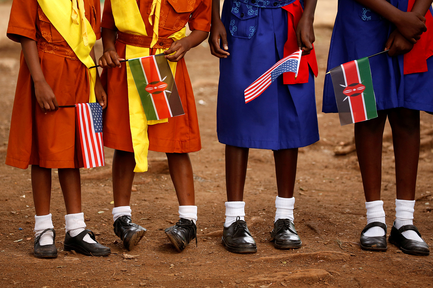 Young girls holding U.S. and Kenyan flags wait to greet U.S. Ambassador Robert Godec at a President's Emergency Plan for AIDS Relief (PEPFAR) project for girls' empowerment in Nairobi on Mar 10, 2018. The photo shows four girls from the stomach down holding flags. REUTERS/Jonathan Ernst