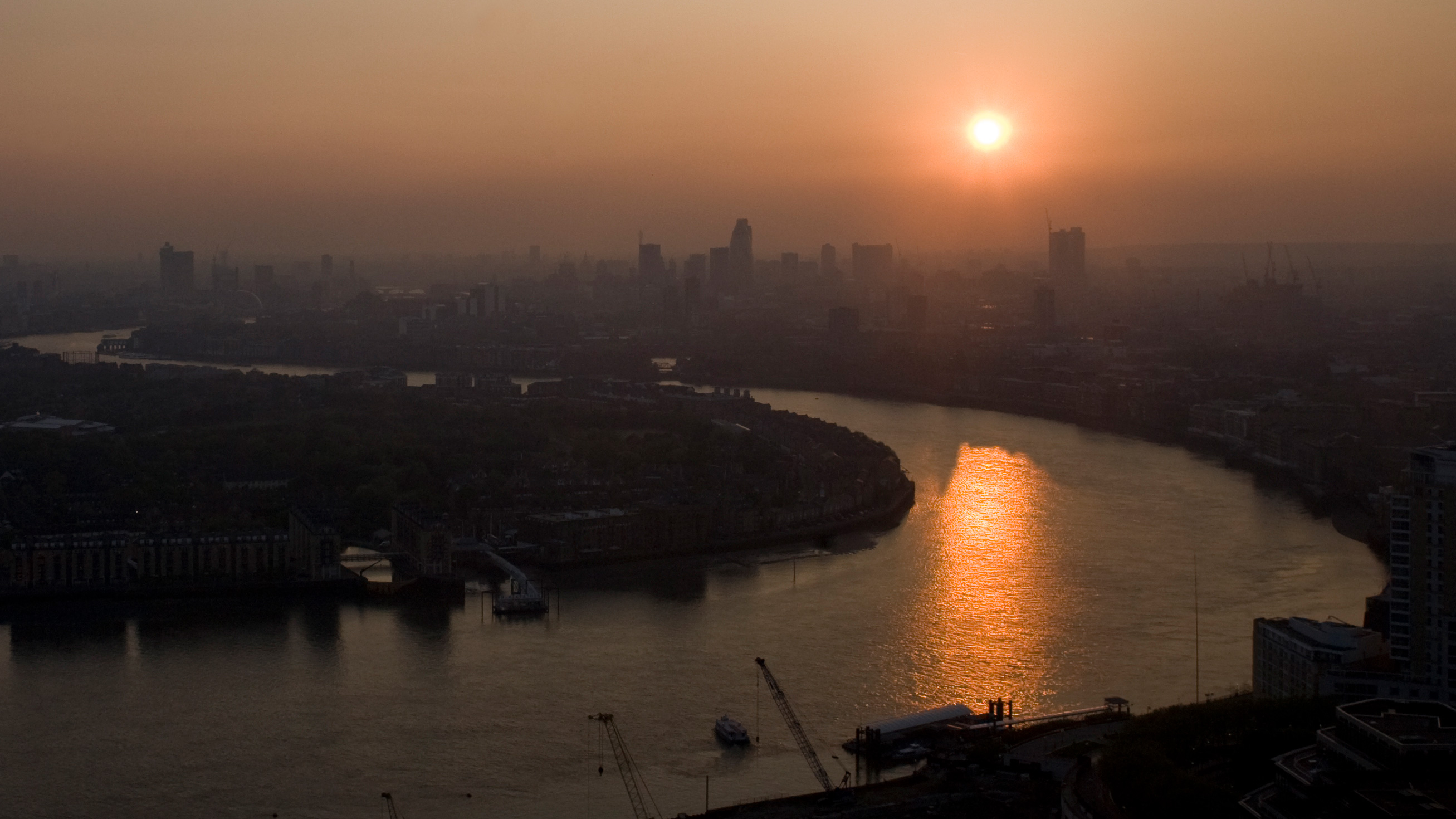The picture shows a high angle shot of London at dusk with the sun setting over the Thames. Smog obscures buildings in the distance.