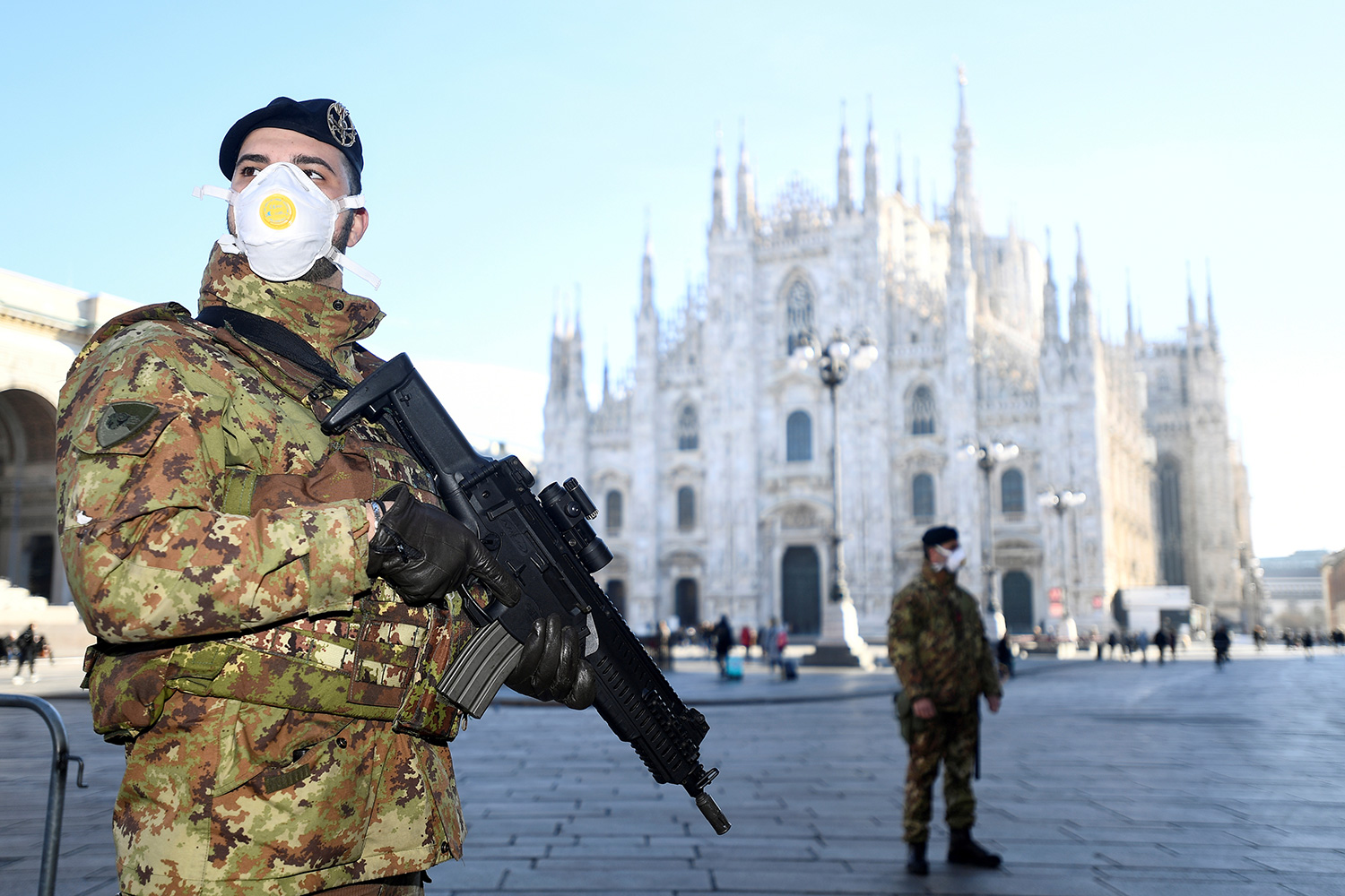 Military officers wearing face masks stand outside Duomo cathedral in Milan, Italy on February 24, 2020. The cathedral was closed by authorities due to the coronavirus outbreak. The photo shows a soldier in full combat gear wearing a mask and holding a military-style assault rifle. In the distance is the iconic architectural tourist destination. REUTERS/Flavio Lo Scalzo