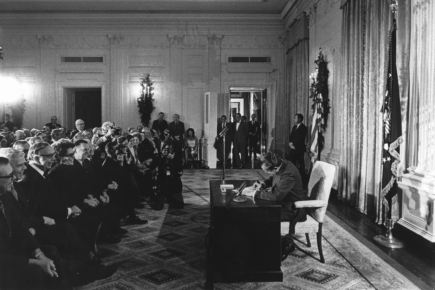 The image shows Nixon at his desk, his head down, signing the bill. In front of him is a large audience of people, many of whom are smiling broadly.