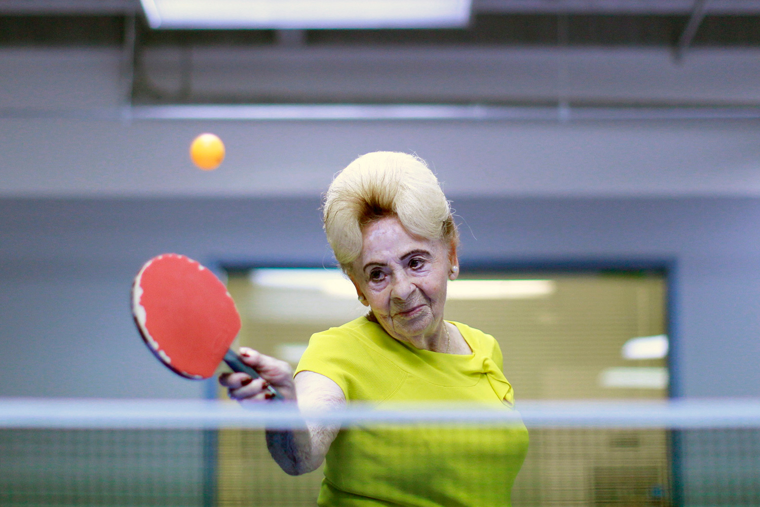Picture shows Betty, who has an old fashioned 1950s-style hairdo, swinging her paddle at a ball.