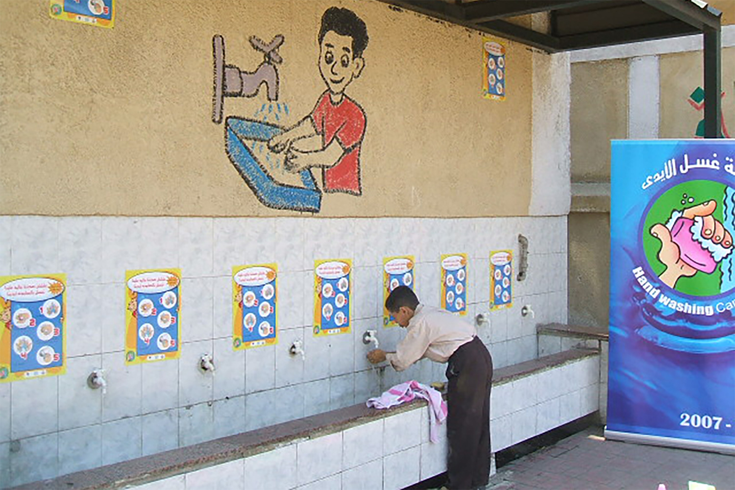 "Entitled, ""Hygiene Program for Egyptian School Children,"" the image shows a boy at a handwadshing station bent over washing his hands. A hygiene propaganda poster can be seen in the backgroung."