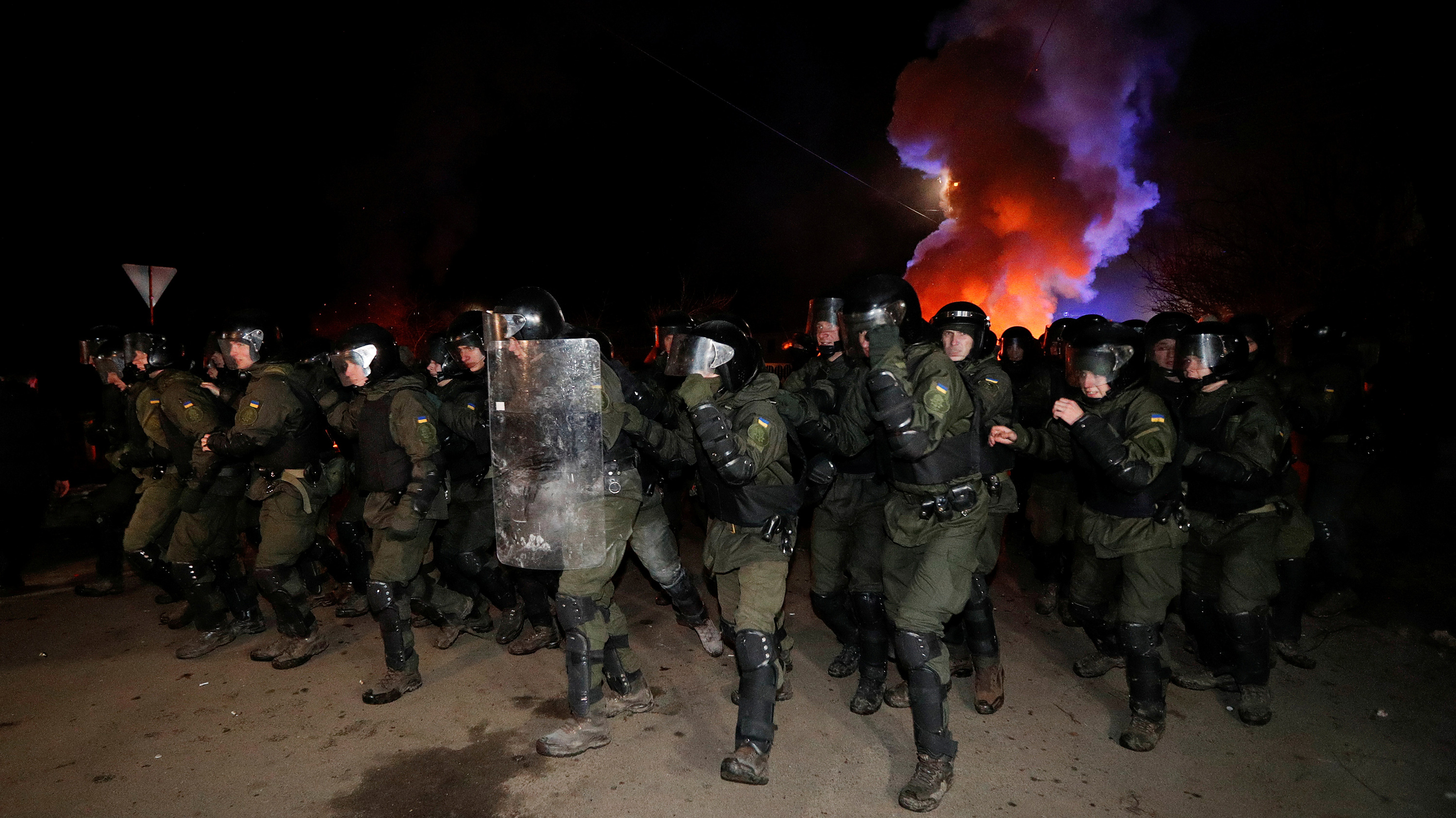 Picture shows more than a dozen officers wearing full riot gear advancing toward the camera at night. Behind them smoke rises and is illuminated by bright orange and blue light, presumably from a police vehicle off camera. This is a stunning photo.