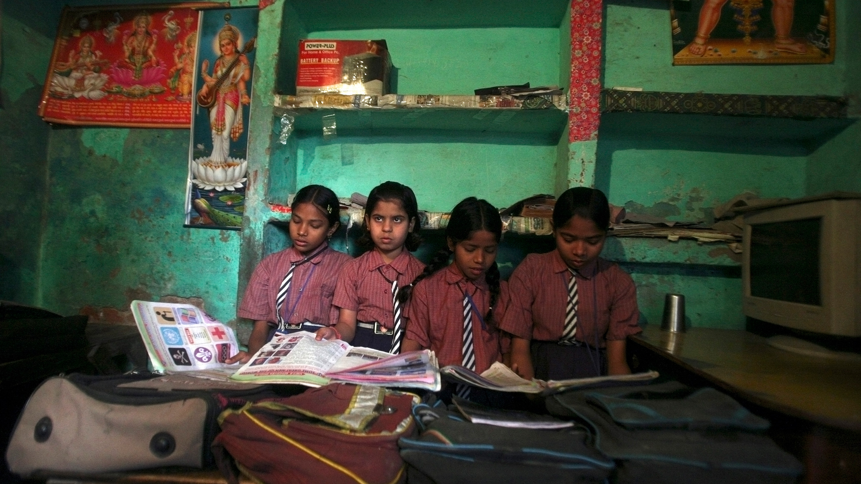 Image show four girls sitting close to each other with their heads buried in books, except one who looks up and off camera. The walls of the school are painted green.